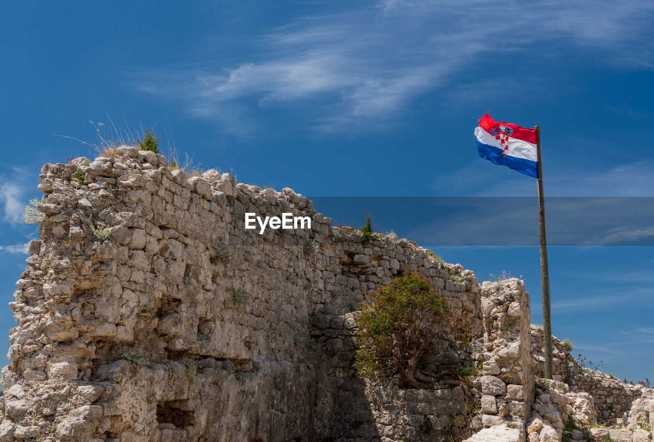 LOW ANGLE VIEW OF FLAG ON ROCK
