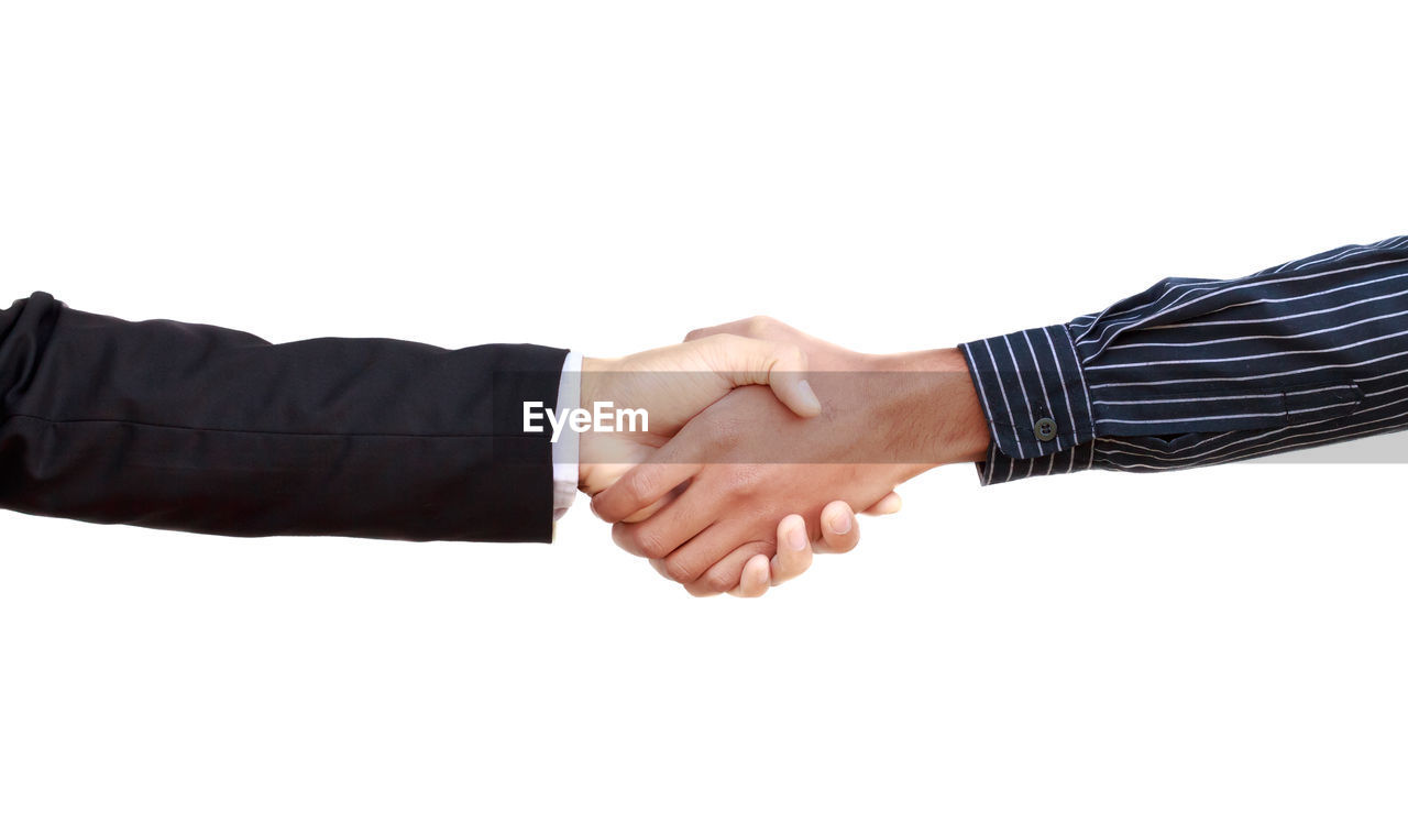 Colleagues shaking hands against white background
