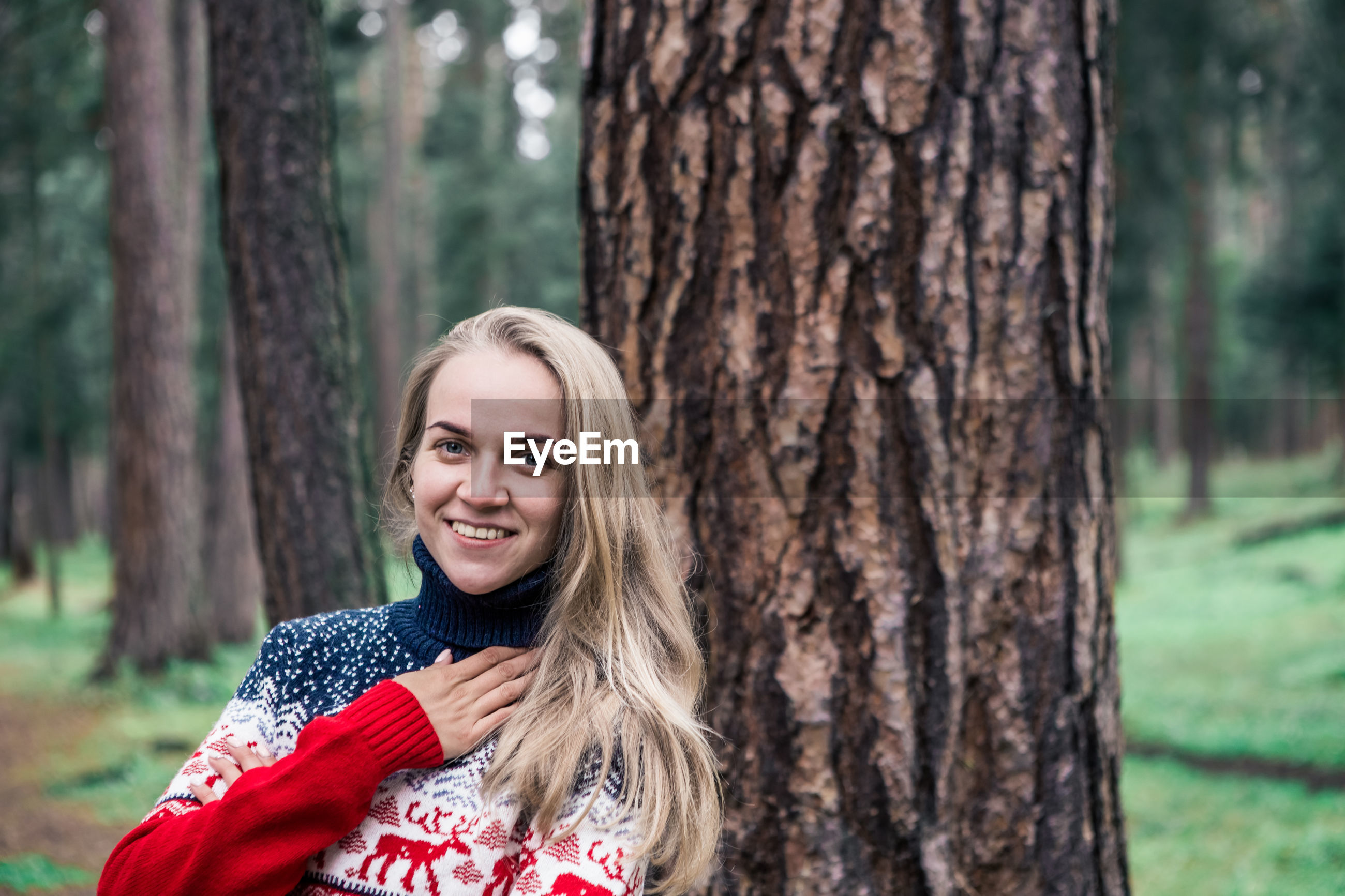 Portrait of woman smiling while standing in forest