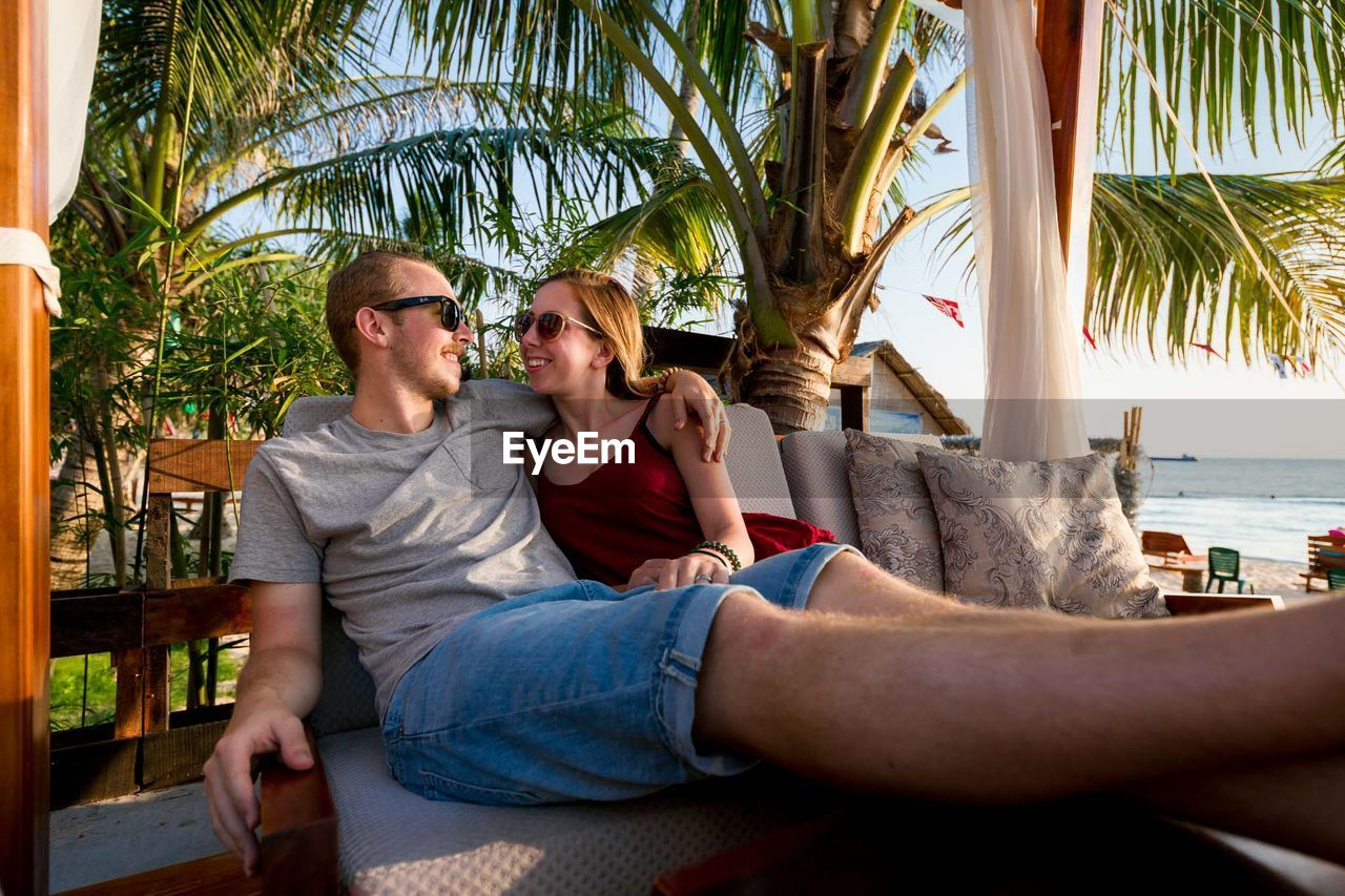 Couple Relaxing On Chair Against Palm Trees At Beach Resort