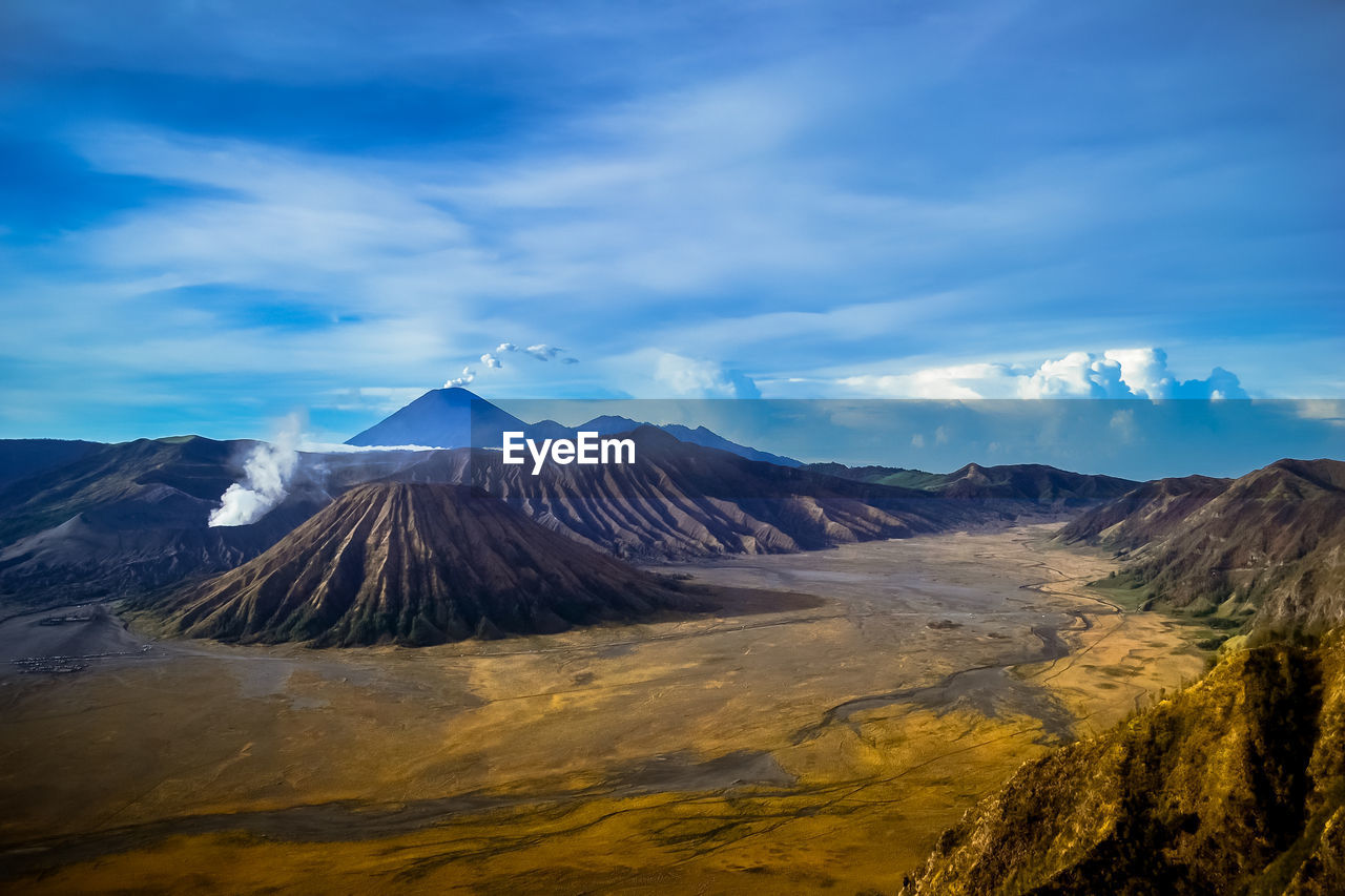 Volcanic Crater And Landscape Against Cloudy Sky