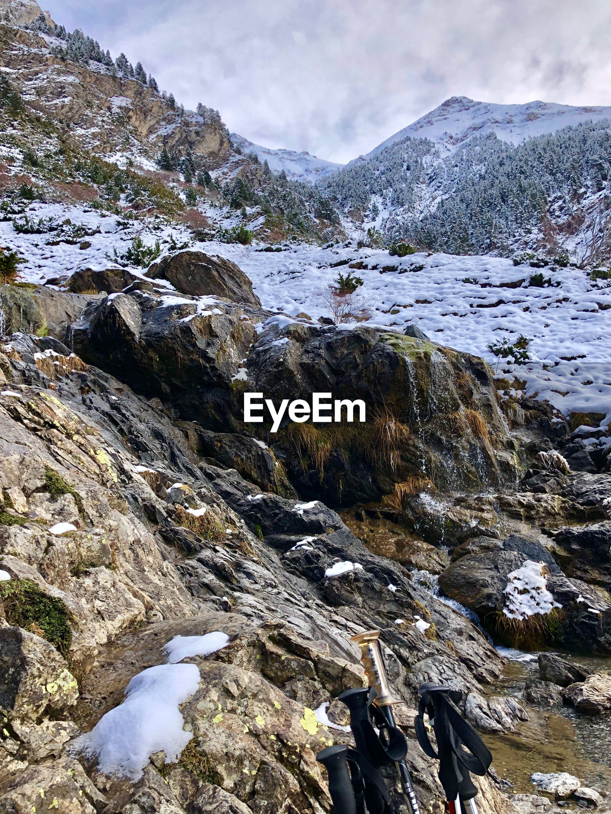 Scenic view of stream flowing through rocks during winter