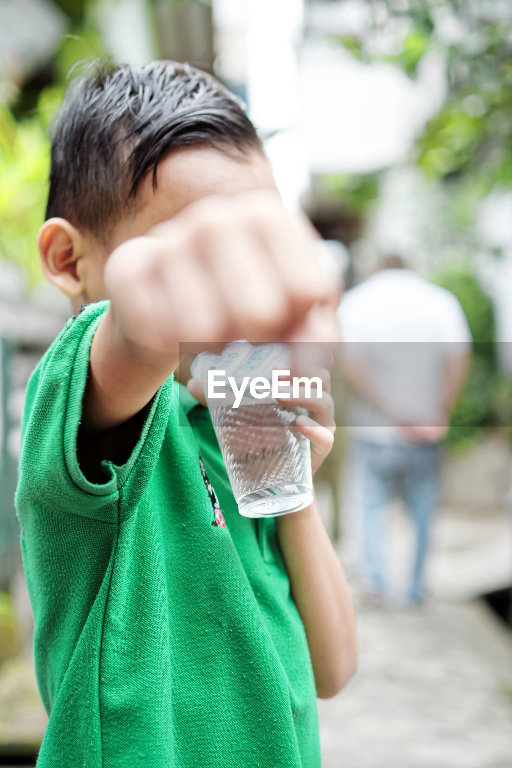 Close-Up Of Boy Punching While Drinking Water From Glass Outdoors