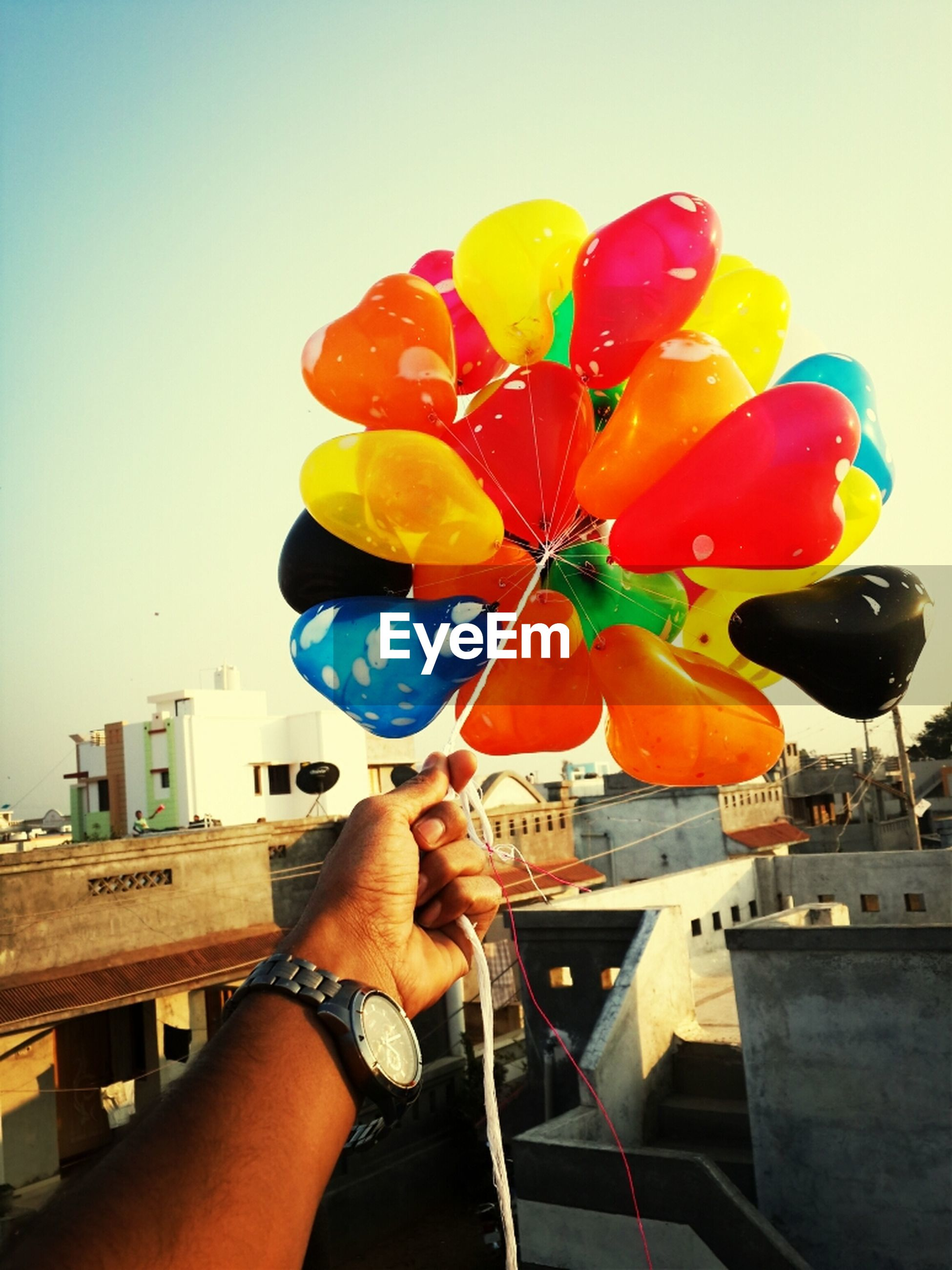 person, holding, cropped, leisure activity, part of, lifestyles, multi colored, human finger, personal perspective, unrecognizable person, toy, yellow, childhood, fun, clear sky, blue, creativity