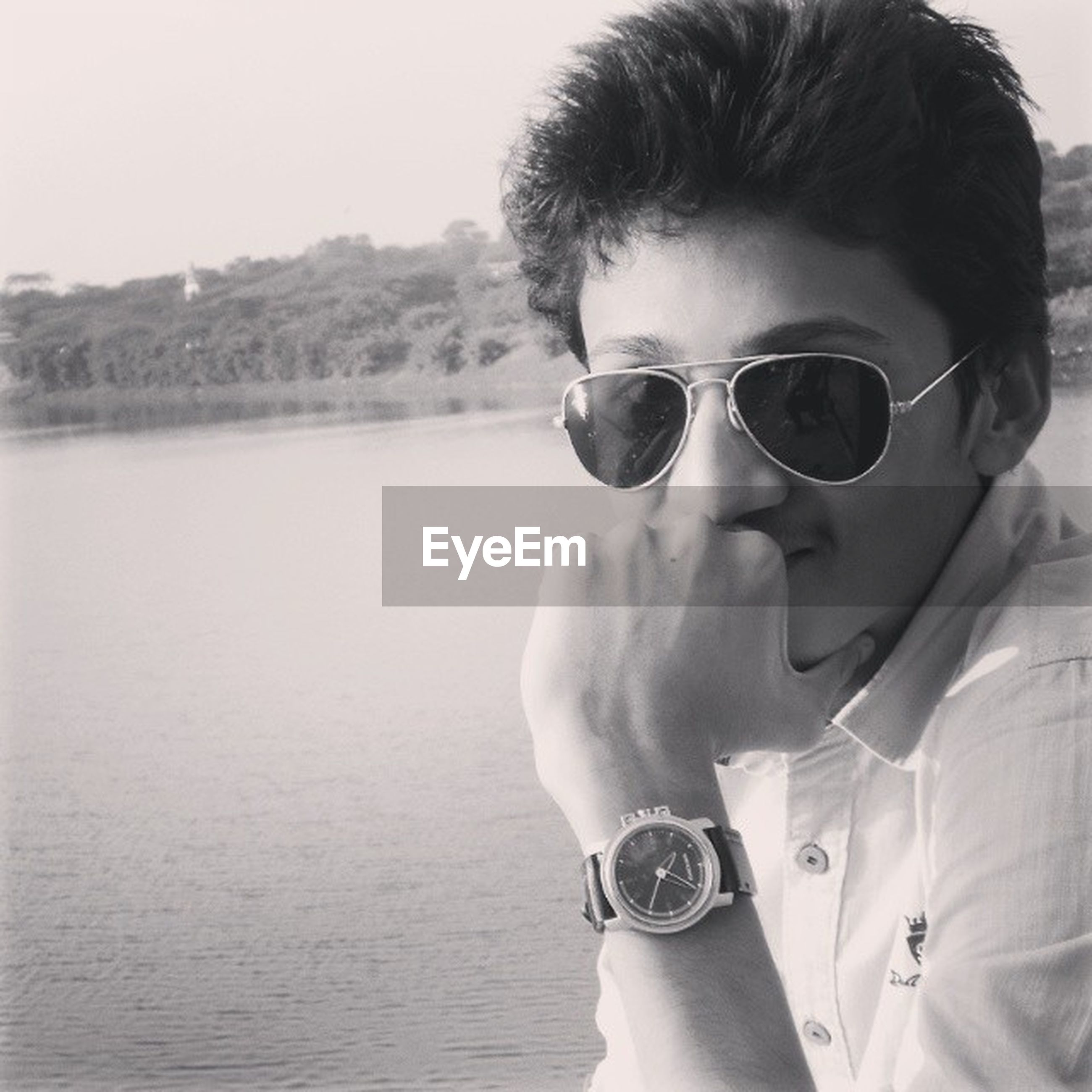 sunglasses, young adult, lifestyles, person, leisure activity, portrait, looking at camera, young men, headshot, front view, casual clothing, smiling, sky, head and shoulders, nature, water, focus on foreground