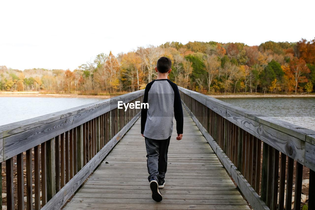 Rear view of boy walking on footbridge over lake