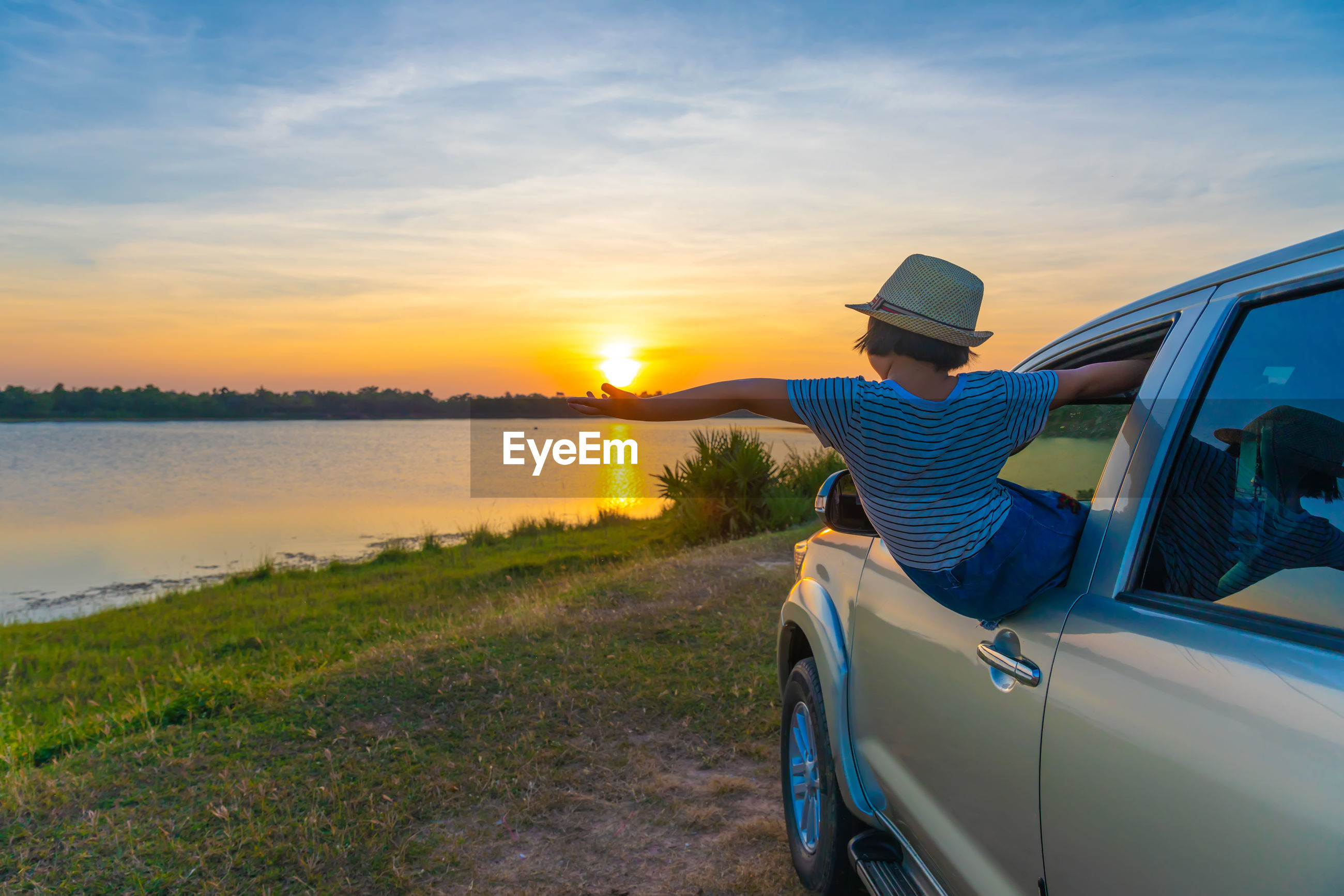 Girl peeking from car window against sky during sunset