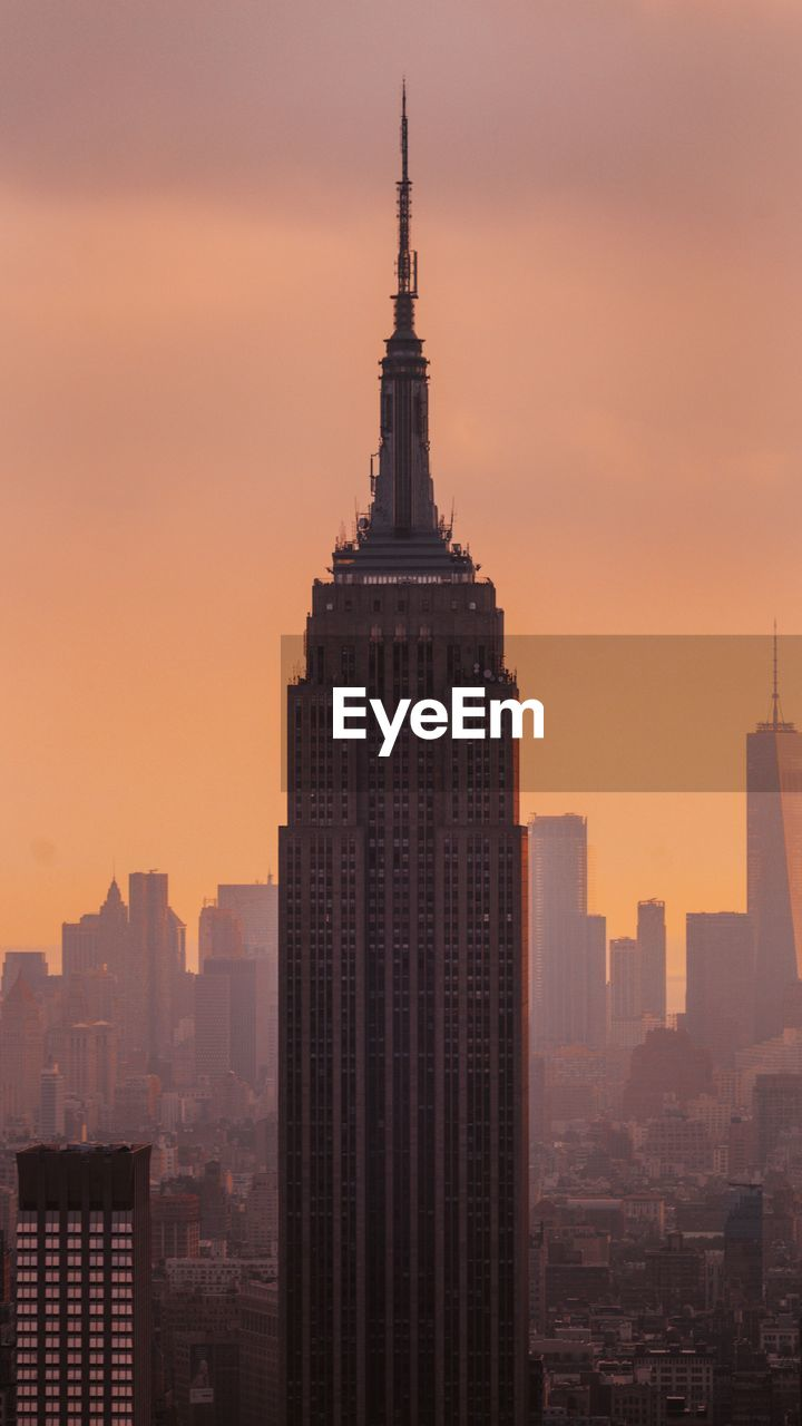 Empire State Building In City Against Orange Sky During Sunset