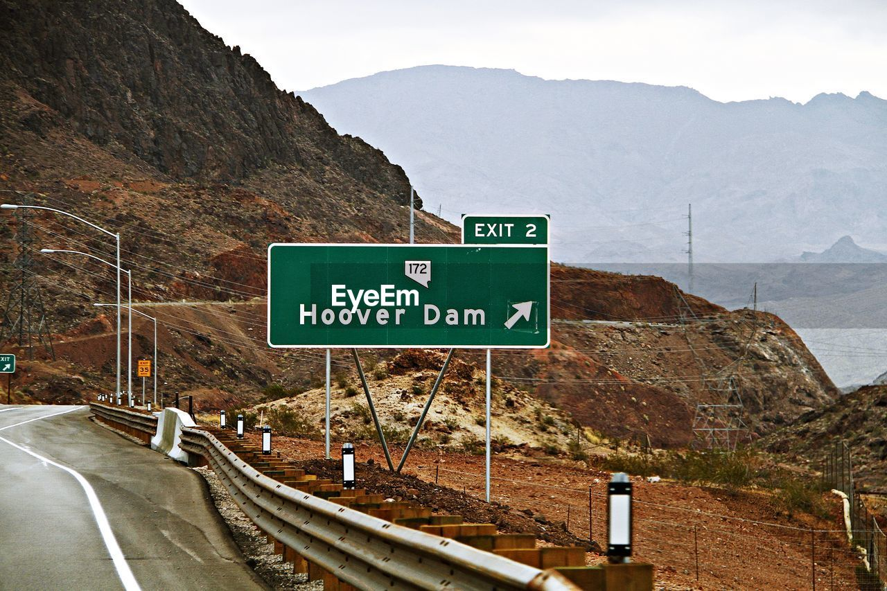 Directional Road Sign On Roadside Against Mountains