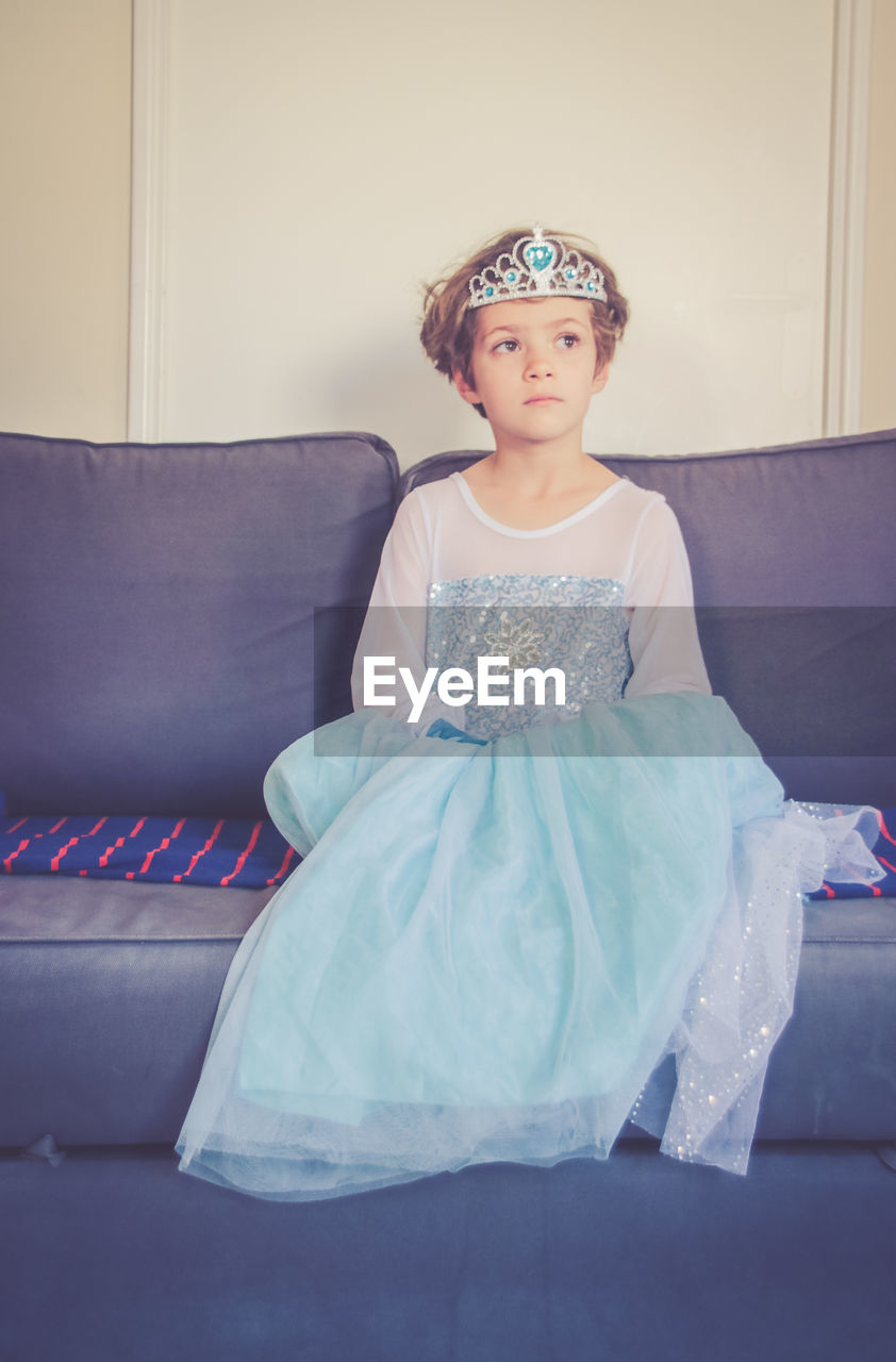 Girl Wearing Costume While Sitting On Sofa At Home