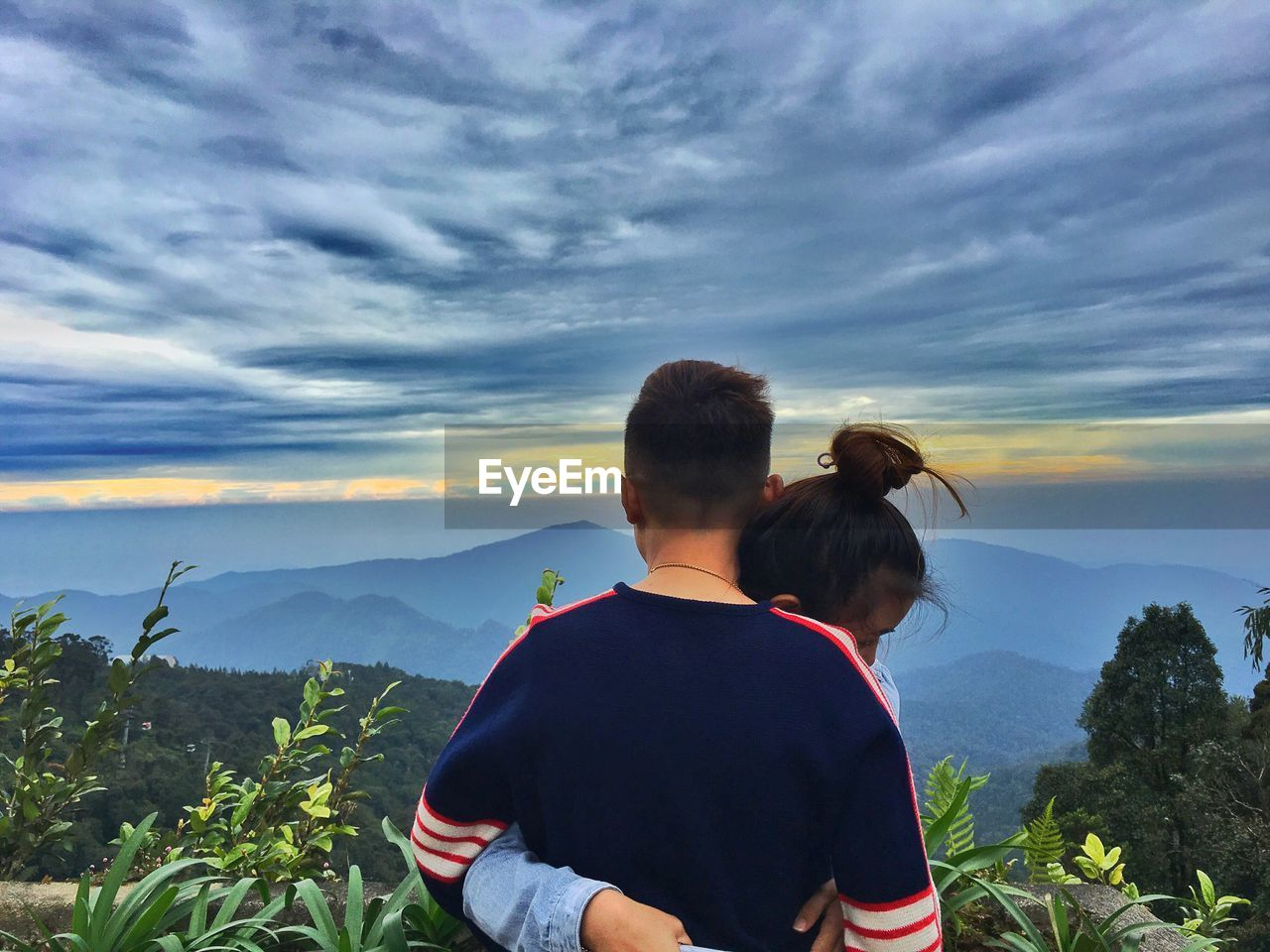 two people, rear view, real people, togetherness, sky, mountain, cloud - sky, love, nature, leisure activity, bonding, looking at view, men, lifestyles, beauty in nature, scenics, casual clothing, women, outdoors, friendship, tree, standing, day, sunset, people