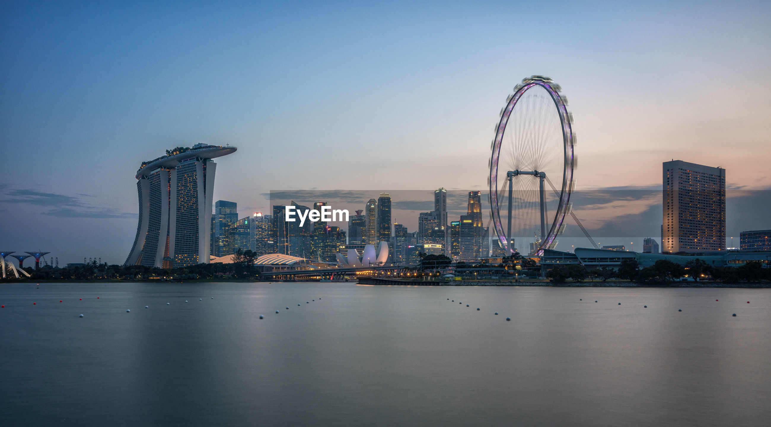 Marina bay sands by bay of water during sunset in city