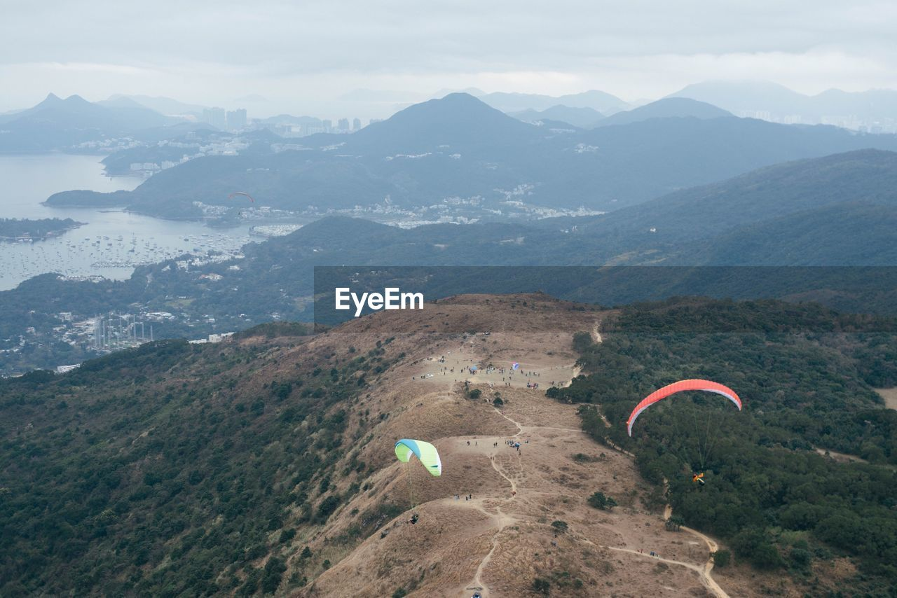 High angle view of people paragliding against mountains