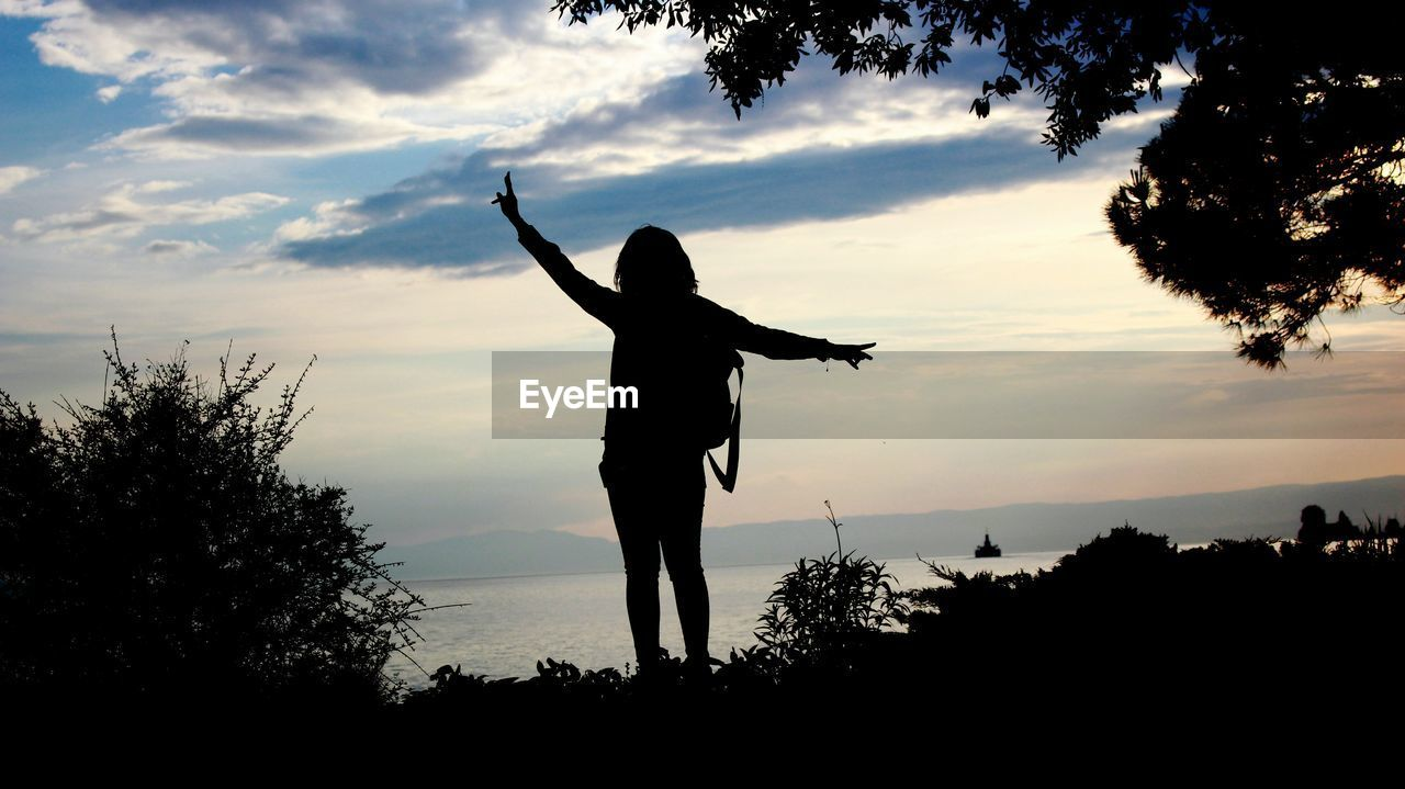 Silhouette woman gesturing while standing at lake against sky during sunset