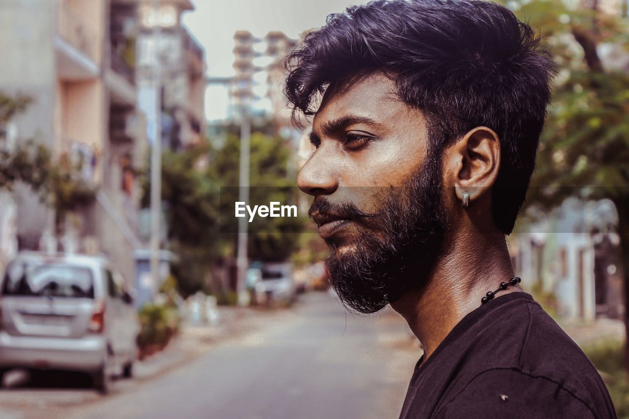 Profile view of man with beard in city