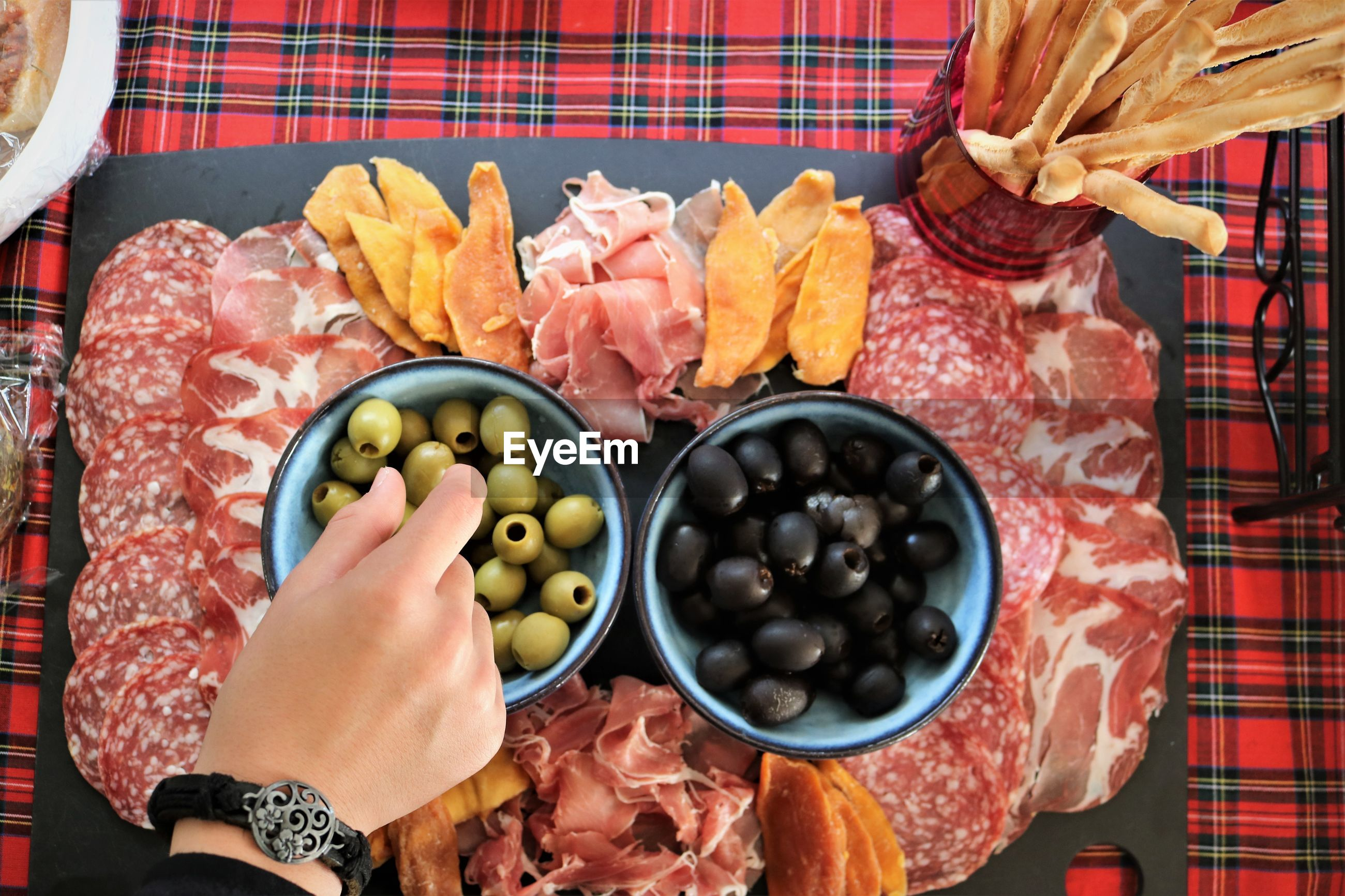 Cropped hand of boy holding olives over bowl and meat in plate