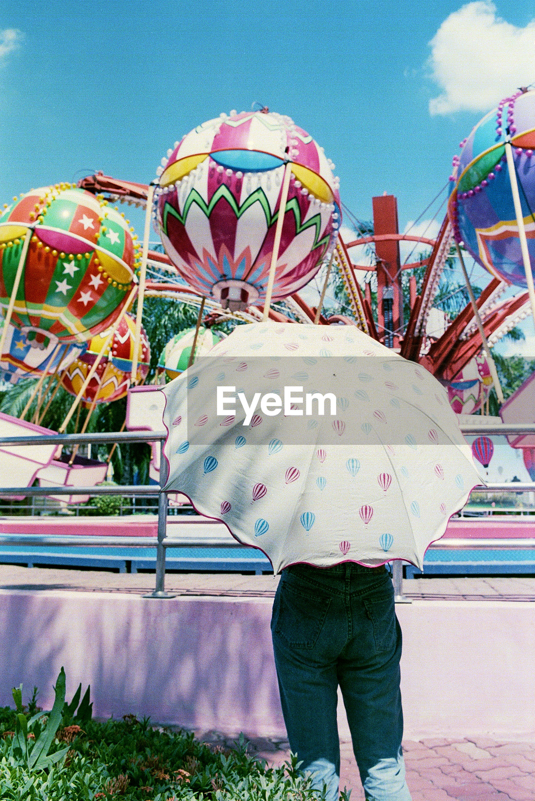 Rear view of person standing under umbrella at amusement park