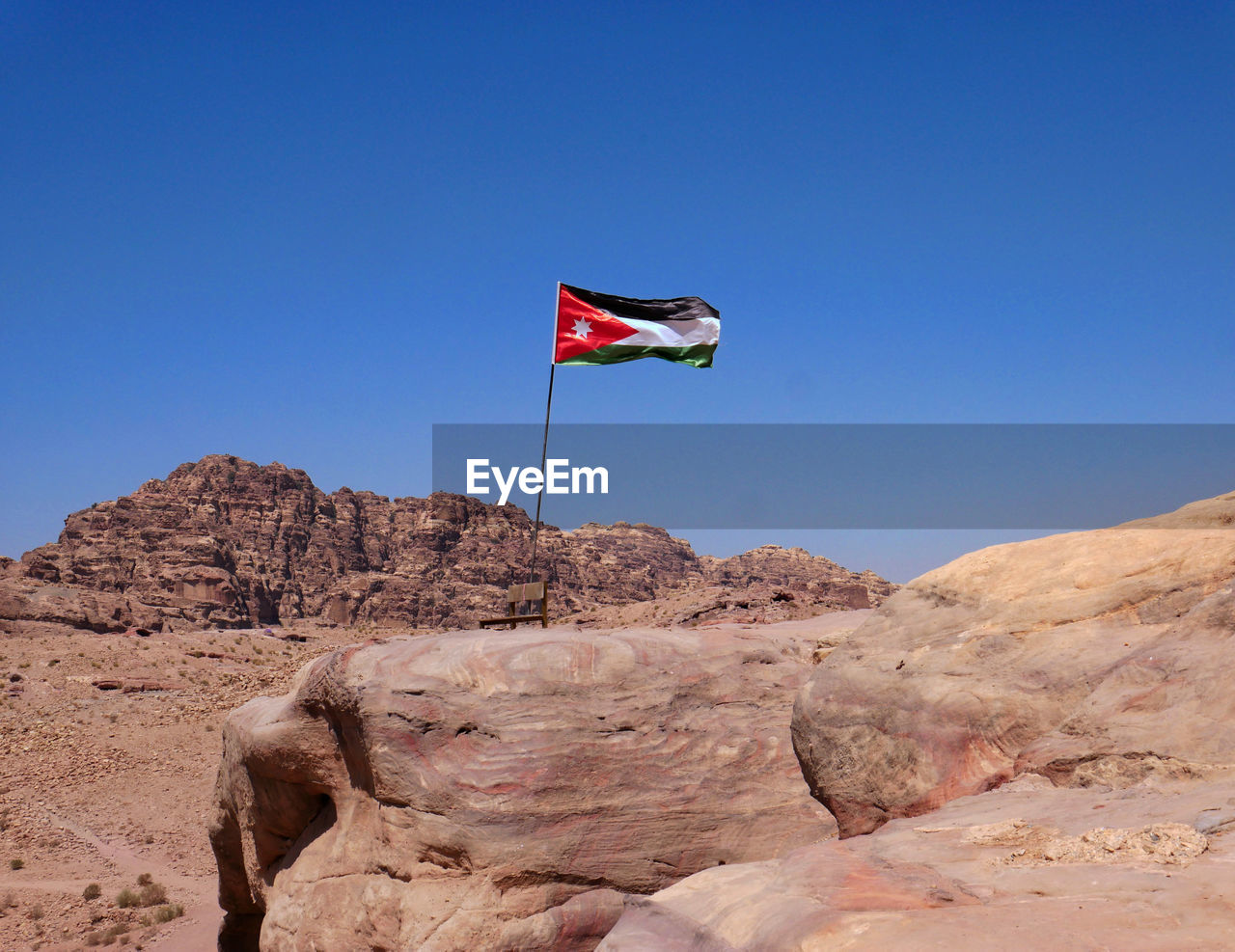 flag, patriotism, sky, environment, rock, rock - object, solid, clear sky, nature, wind, scenics - nature, blue, day, rock formation, mountain, copy space, no people, pride, non-urban scene, outdoors, arid climate, independence, climate, formation, national icon