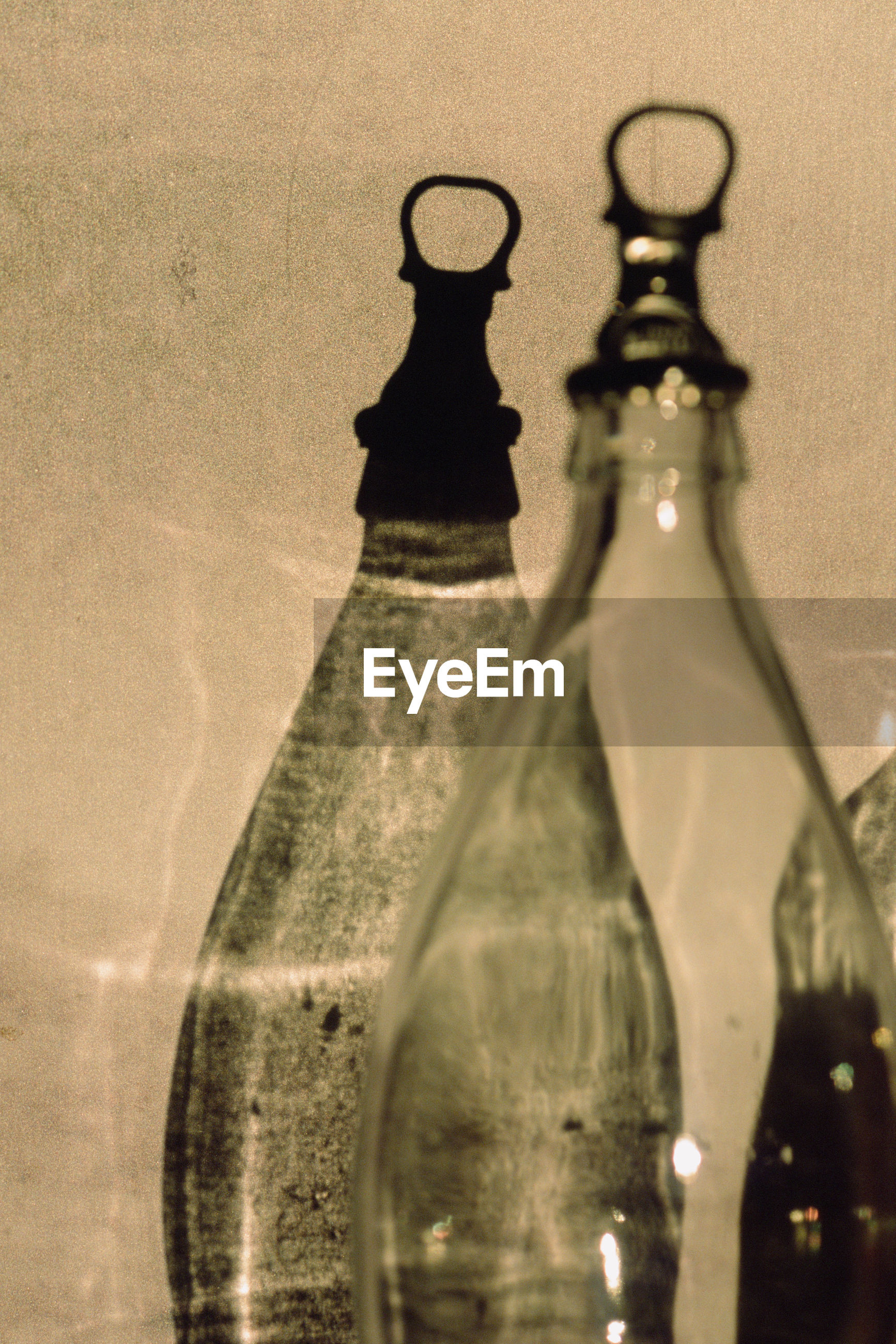 Close-up of empty bottles against wall