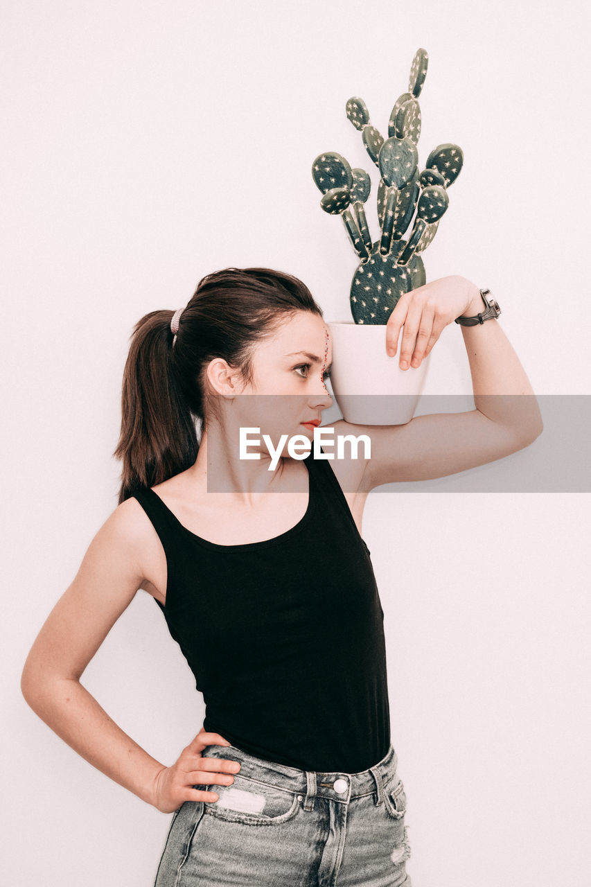 Young woman with potted plant and hand on hip standing against white background