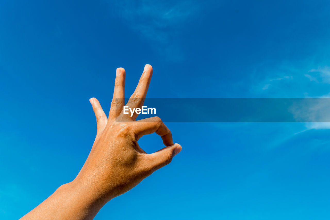 Cropped Hand Gesturing Ok Sign Against Blue Sky