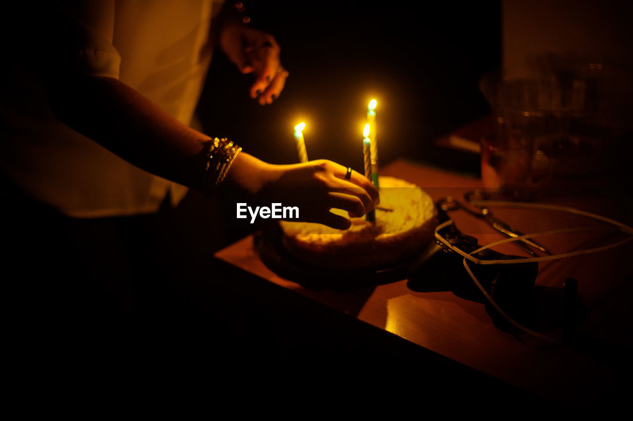 Midsection of woman putting illuminated candle on cake in darkroom