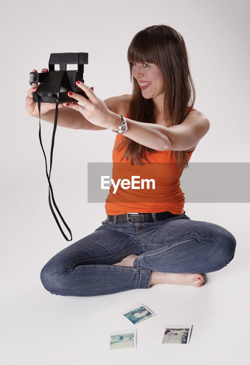 Beautiful woman taking selfie through camera against white background