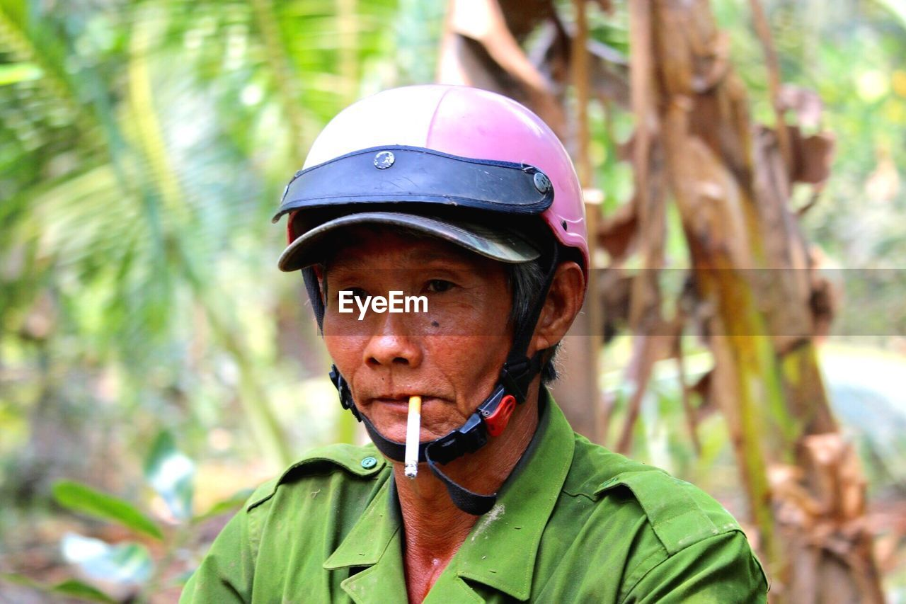 portrait, headshot, one person, tree, focus on foreground, helmet, front view, real people, plant, leisure activity, day, adult, mature adult, looking at camera, headwear, men, forest, lifestyles, green color, mature men, outdoors