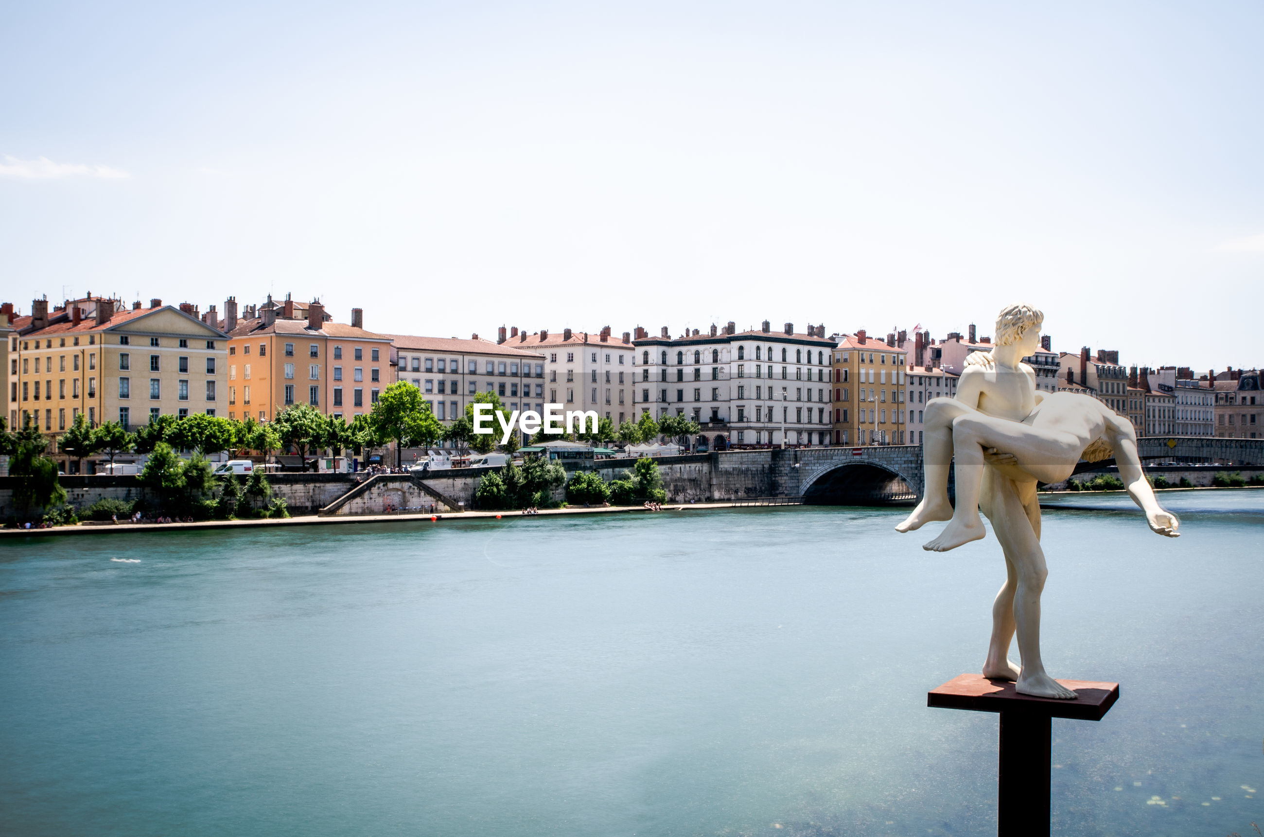 Statue by lyon cityscape against clear sky