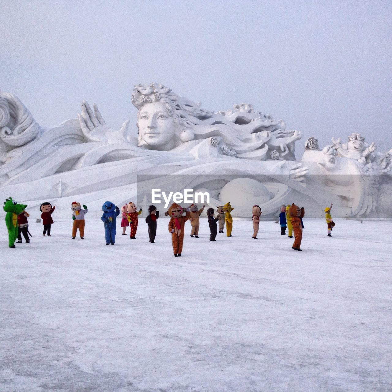 sculpture, human representation, statue, male likeness, winter, large group of people, cold temperature, men, snow, leisure activity, low angle view, day, outdoors, real people, nature, sky, people