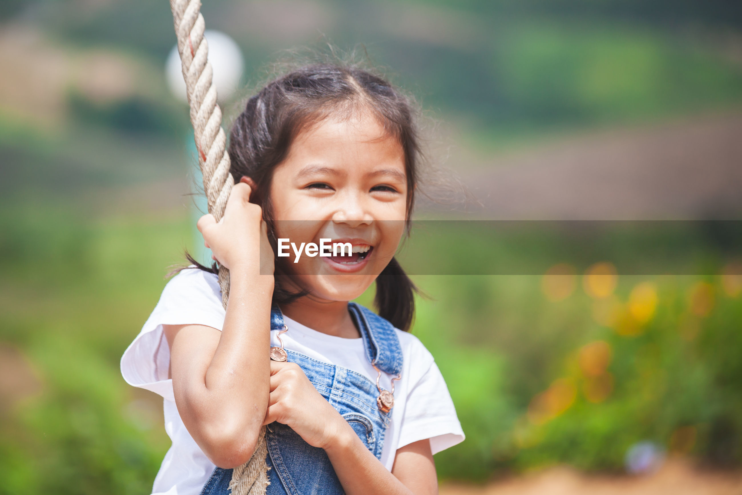 Cheerful girl swinging on rope swing at playground