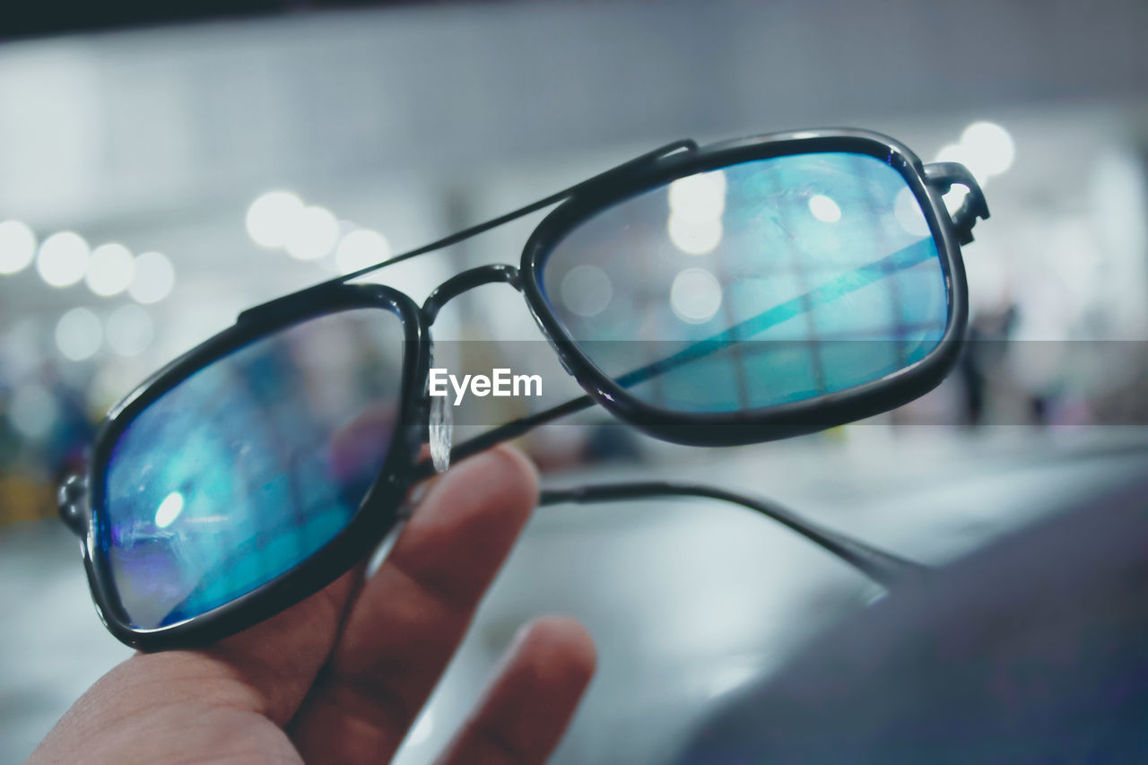 eyewear, vision care, hand, glasses, blue, one person, close-up, sunglasses, reflection, holding, fashion, focus on foreground, day, fashion accessory, outdoors, glass, adult, eyeglasses, nature, city, protection