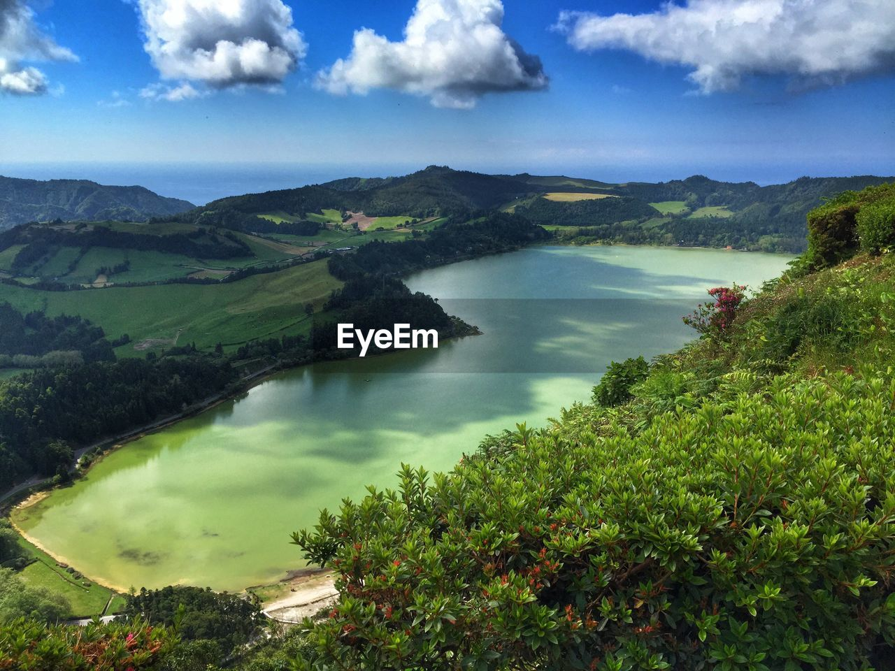 High Angle View Of Lagoa Das Furnas Amidst Green Landscape Against Sky