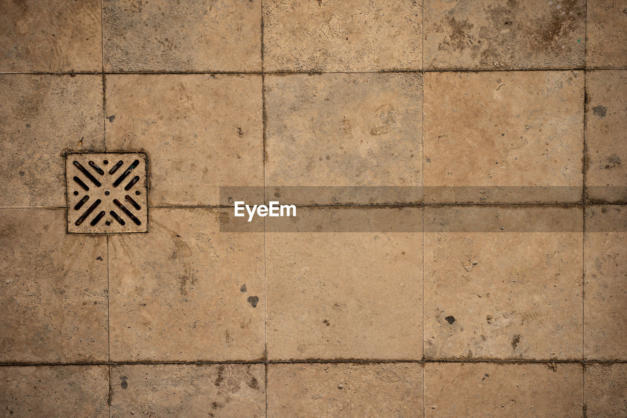 sign, wall - building feature, architecture, communication, flooring, tile, no people, backgrounds, pattern, symbol, built structure, stone material, tiled floor, textured, close-up, solid, shape, full frame, concrete, outdoors