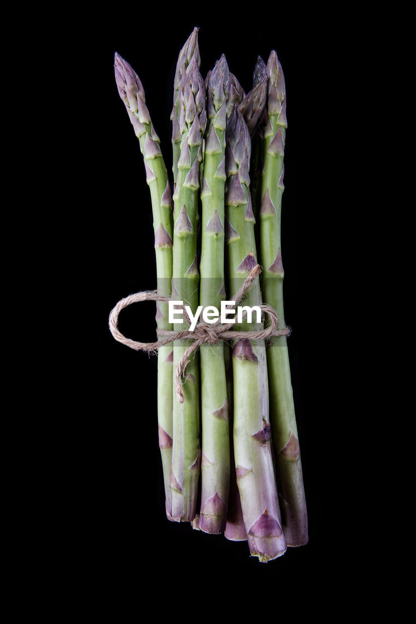 Close-up of tied asparagus against black background
