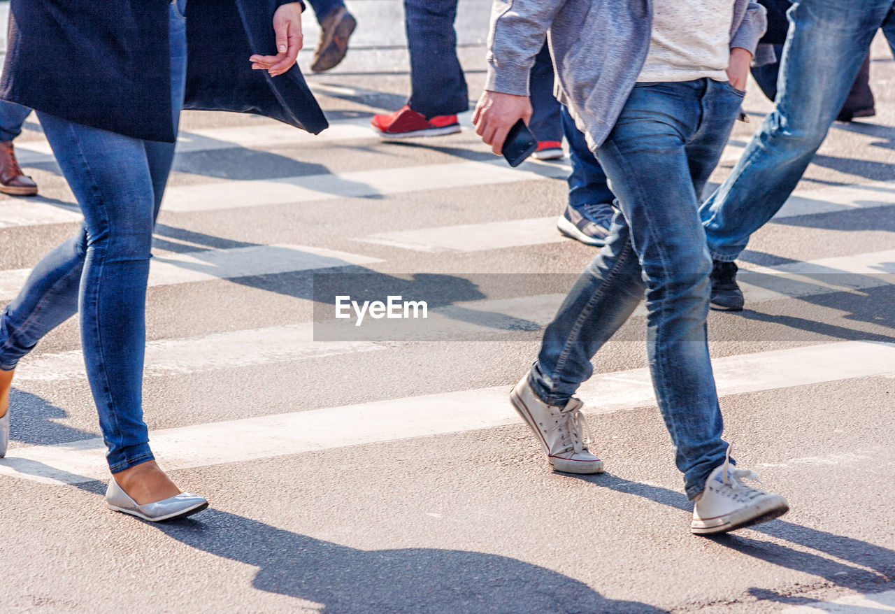 low section, sunlight, shadow, human leg, group of people, body part, day, human body part, jeans, men, togetherness, motion, road, nature, casual clothing, city, shoe, adult, lifestyles, real people, outdoors, human limb
