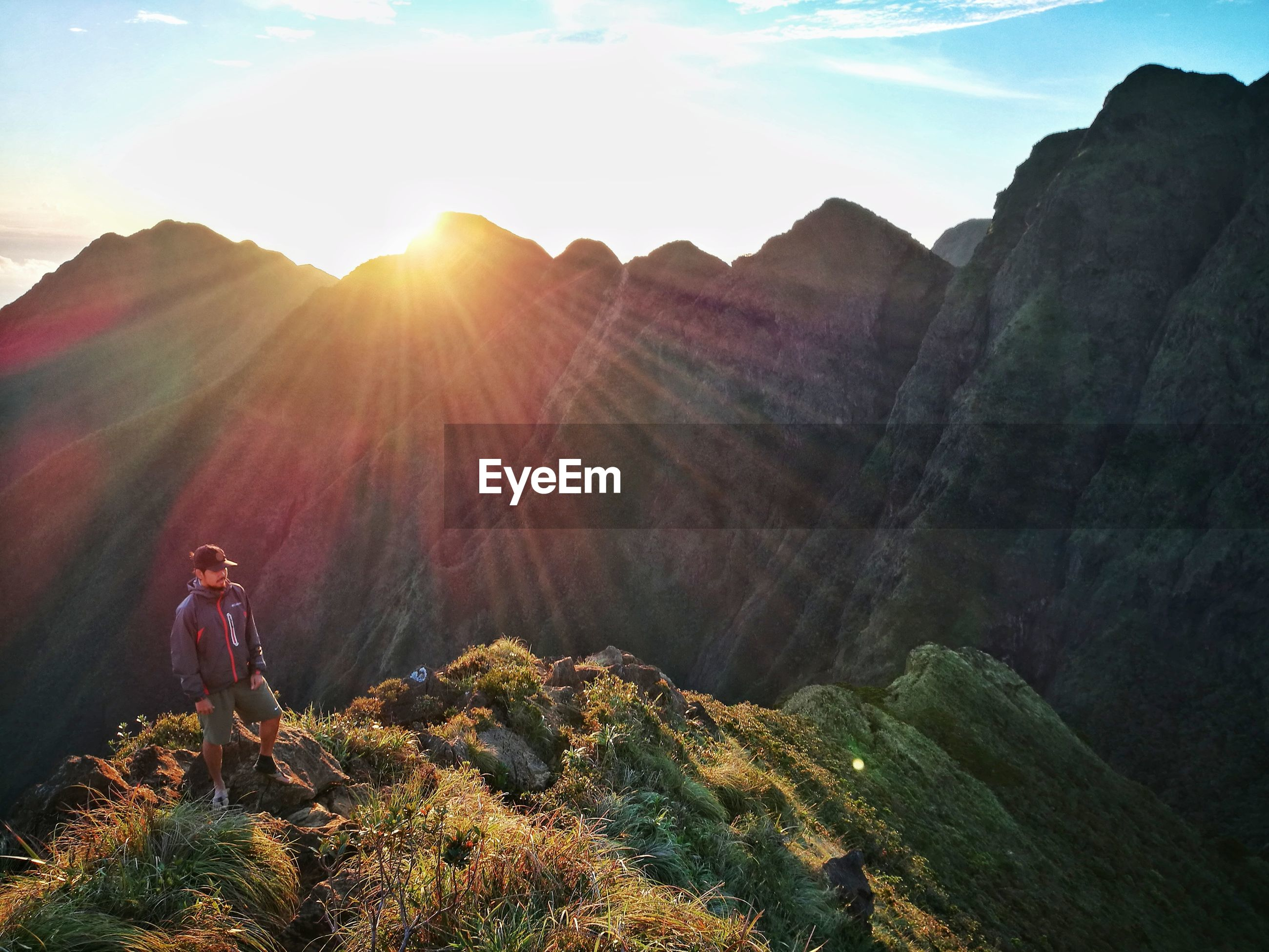 Full length of male hiker standing on top of mountain during sunset