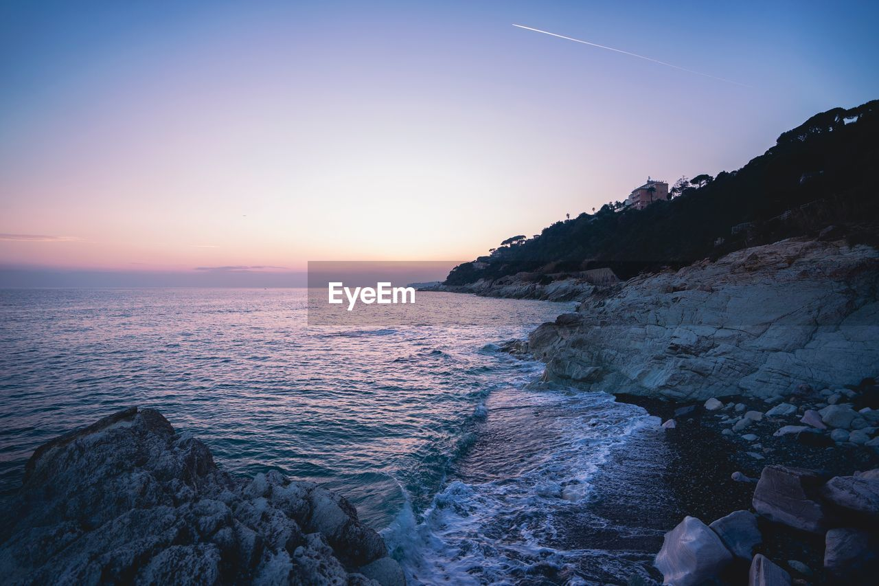 sky, water, sea, scenics - nature, beauty in nature, sunset, rock, rock - object, solid, tranquil scene, tranquility, nature, beach, idyllic, horizon, land, no people, clear sky, horizon over water, outdoors, rocky coastline