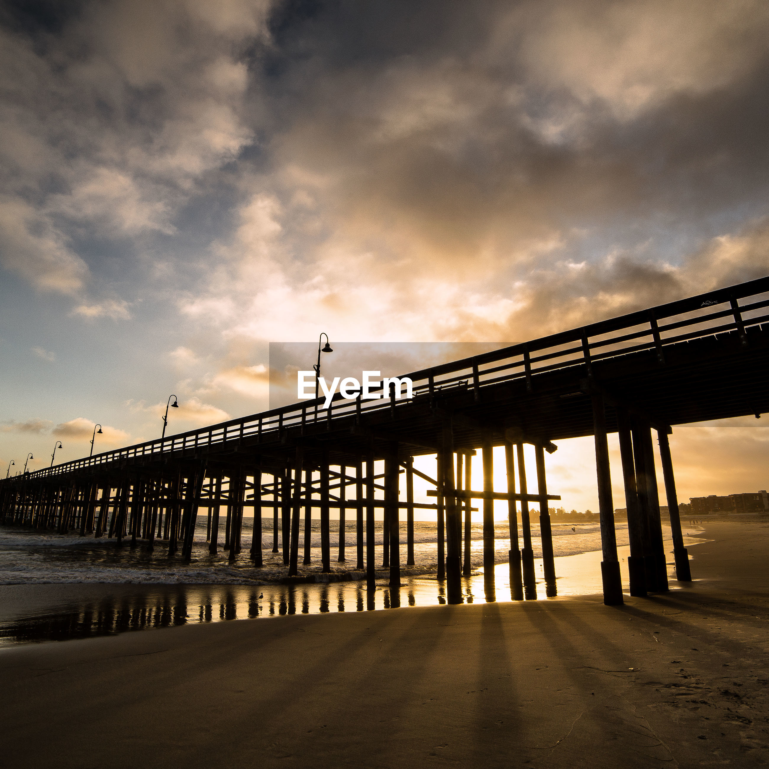 Low angle view of pier on beach during sunset