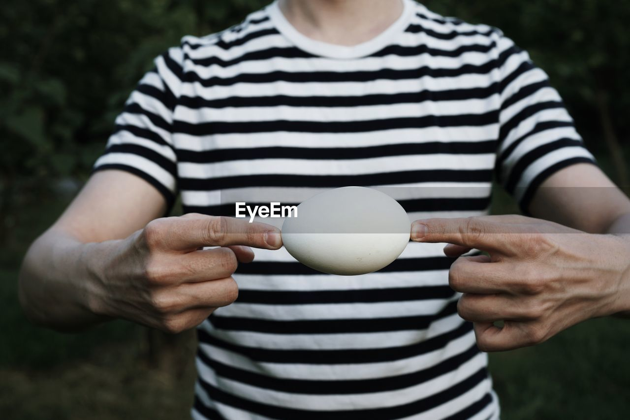Midsection Of Man Holding Egg