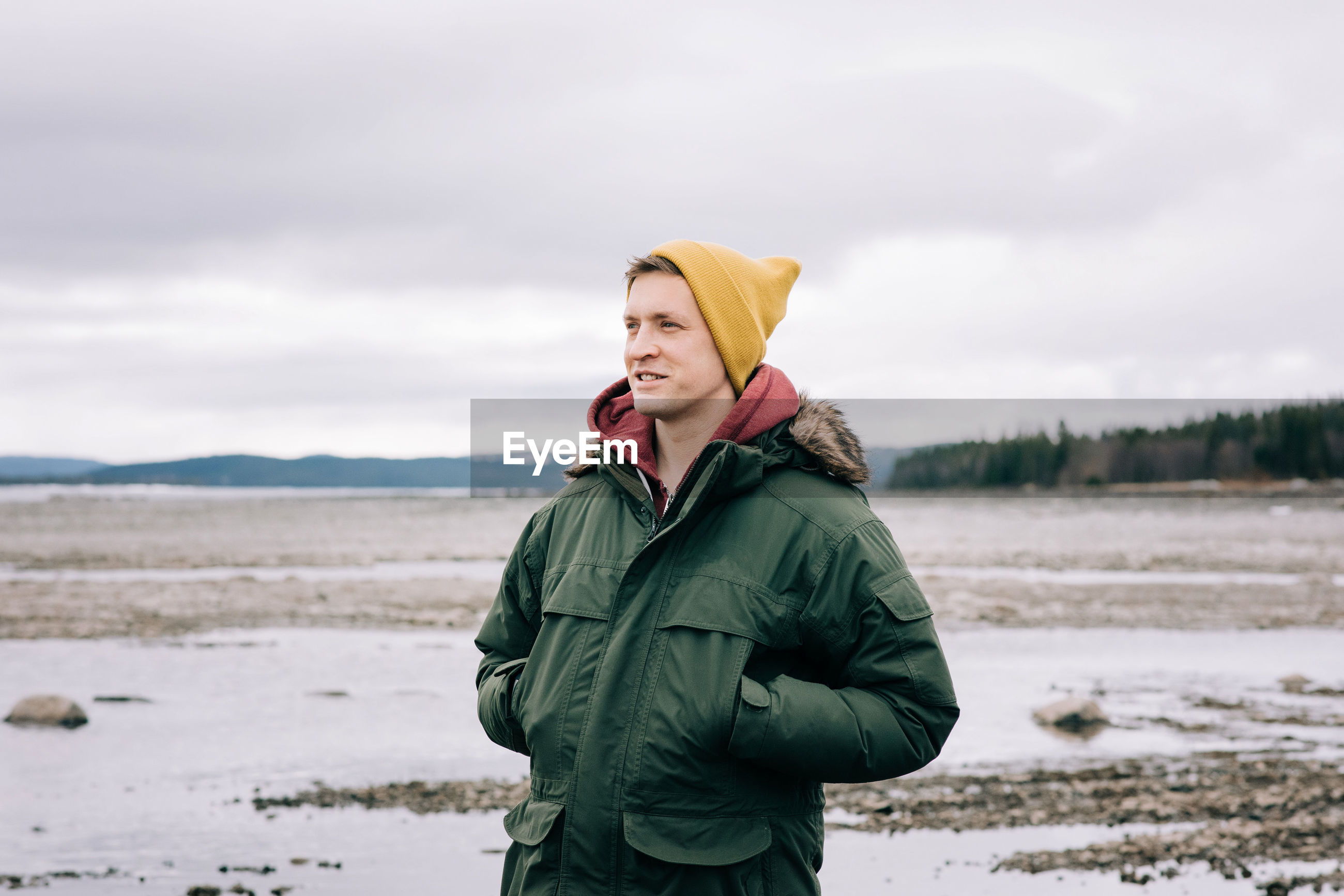 YOUNG MAN STANDING ON SNOW COVERED LAND