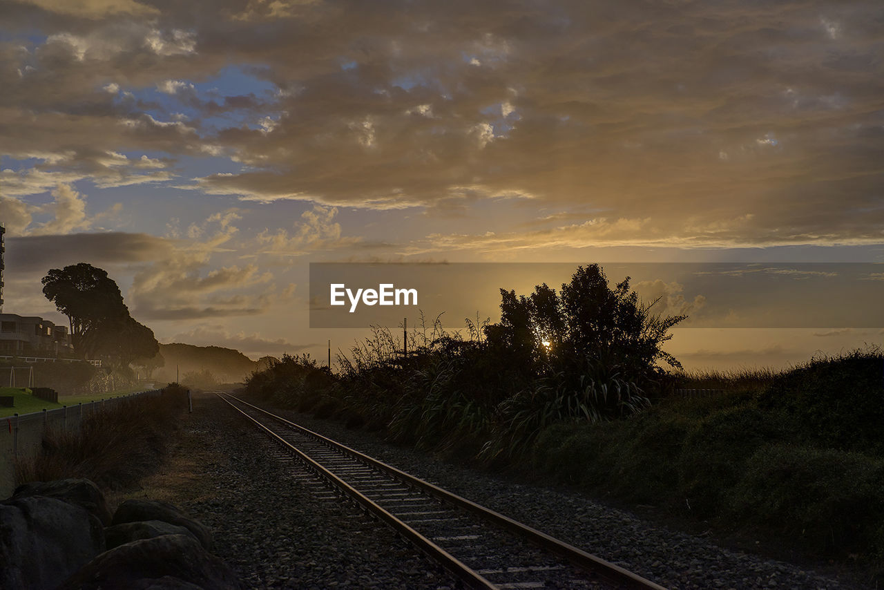 Railroad Track By Silhouette Trees Against Sky During Sunset