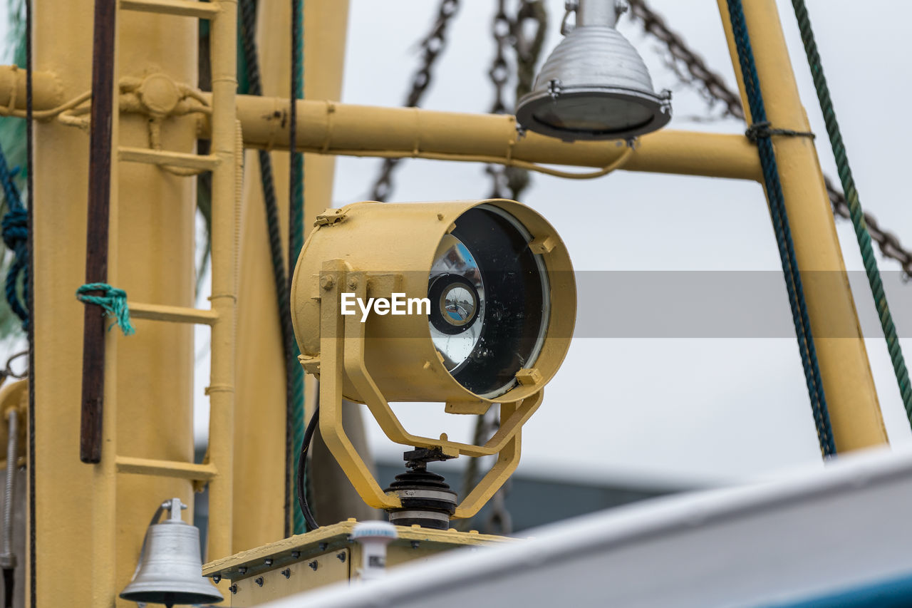 technology, metal, low angle view, industry, no people, day, selective focus, close-up, connection, surveillance, machinery, security, focus on foreground, yellow, outdoors, pipe - tube, equipment, protection, architecture, safety, electrical equipment