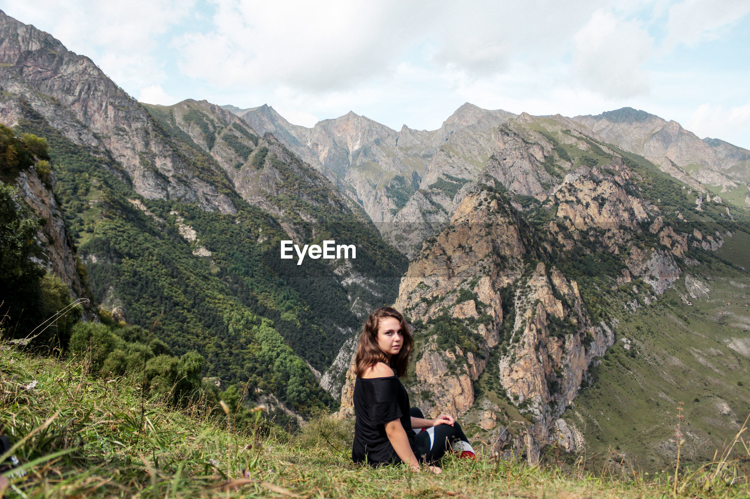 Portrait of young woman sitting against mountain range