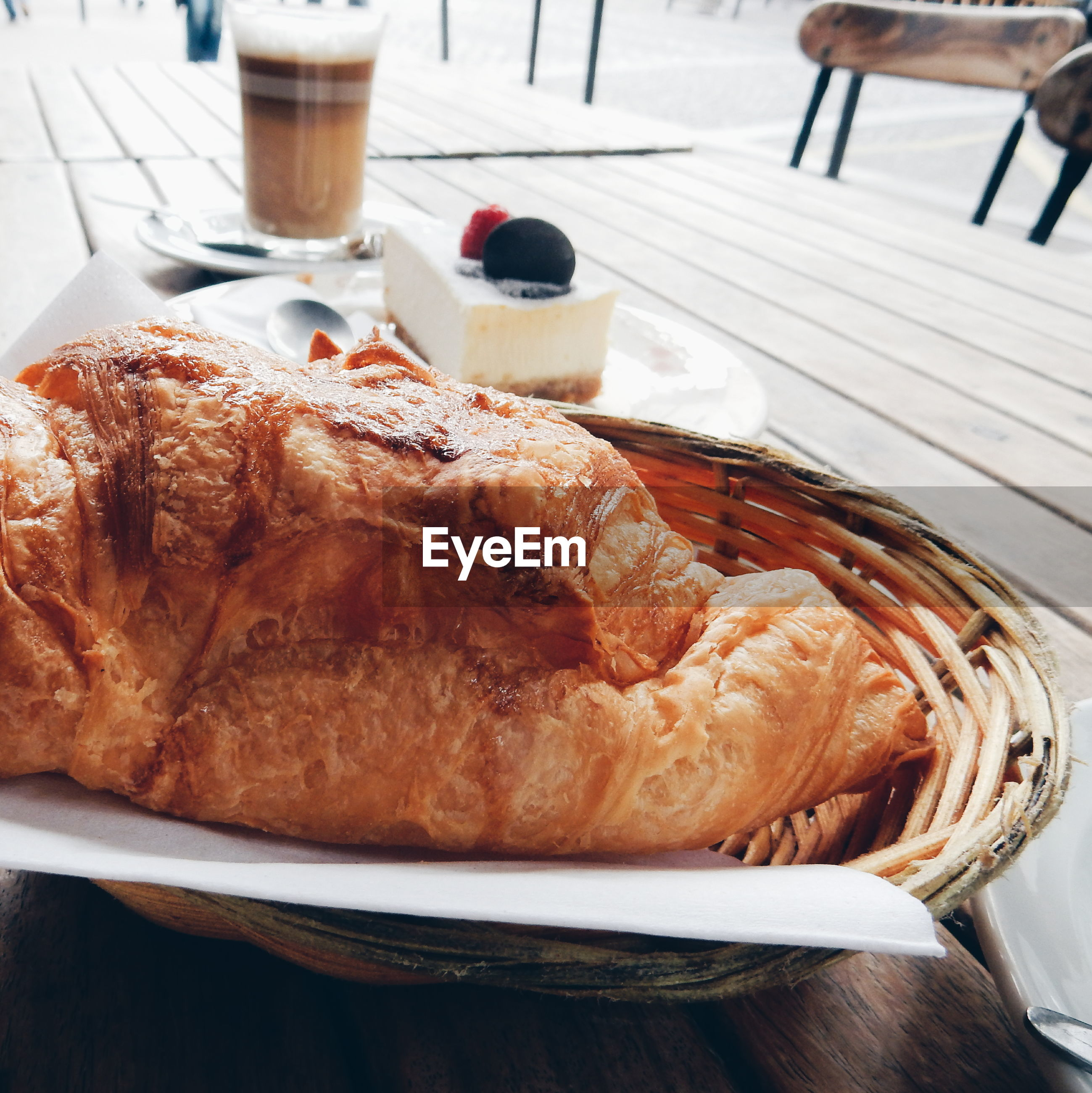 Close-up of croissant with cake and drink served on table