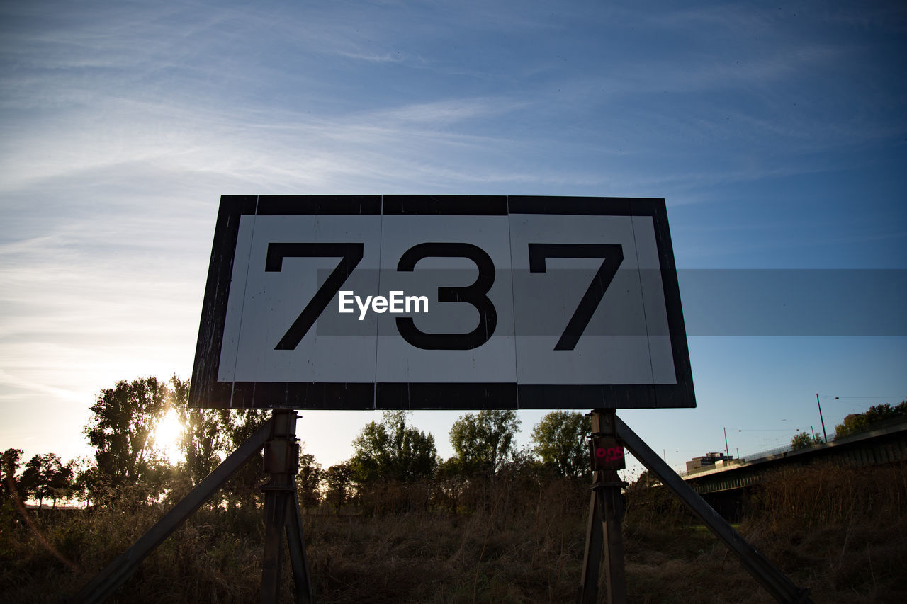 text, communication, no people, sky, road sign, low angle view, day, outdoors, nature, tree, close-up