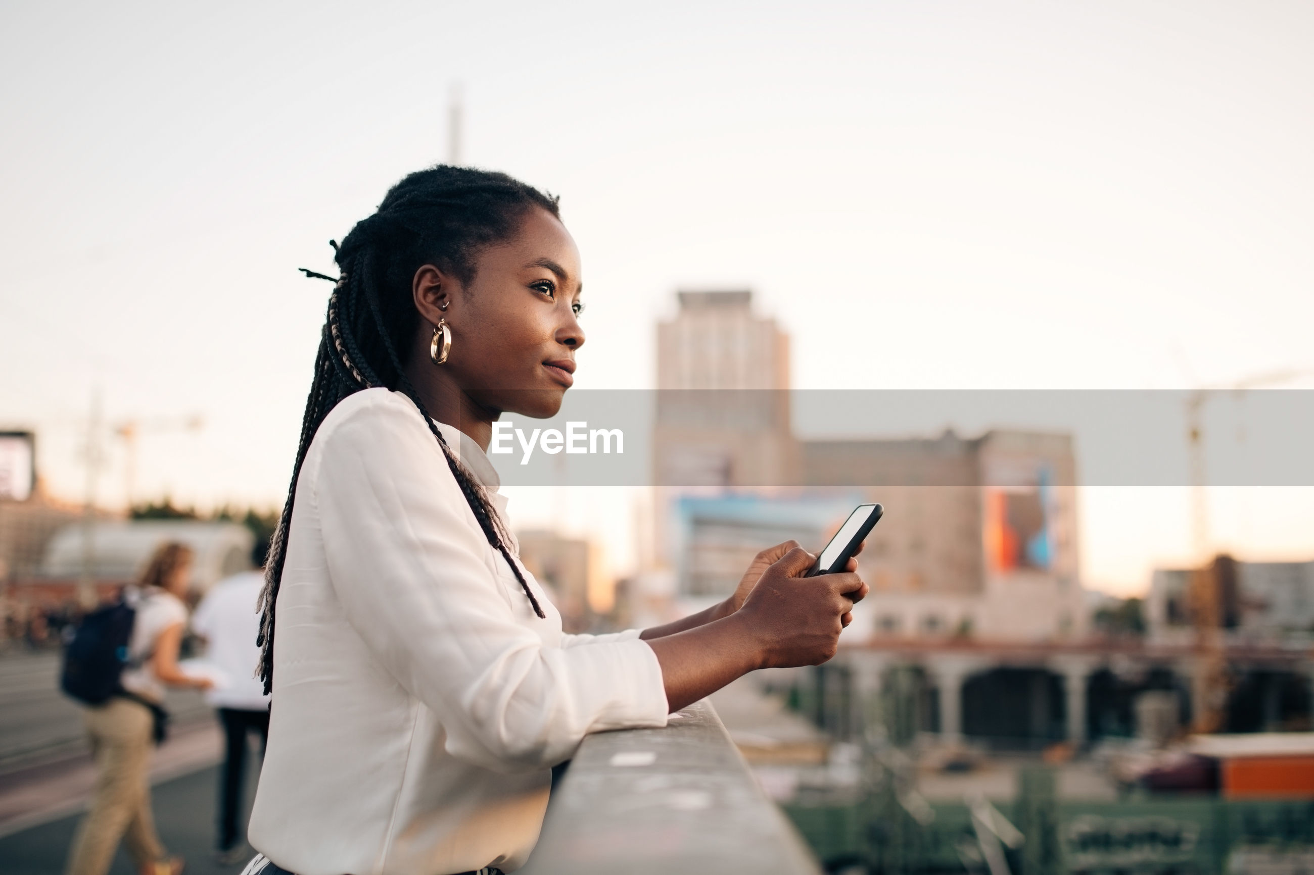 SIDE VIEW OF YOUNG WOMAN USING SMART PHONE AGAINST SKY