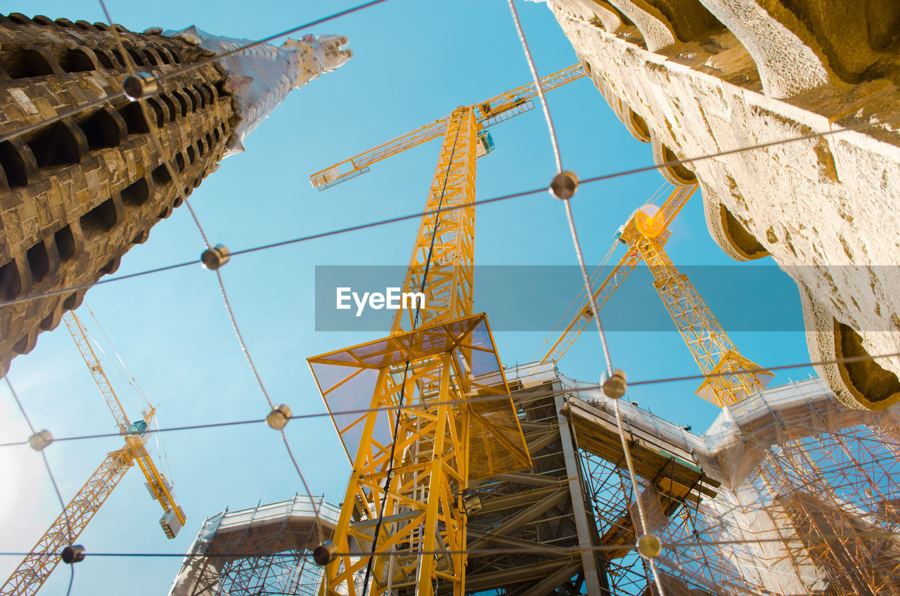 Low Angle View Of Yellow Metallic Cranes At Sagrada Familia Against Sky