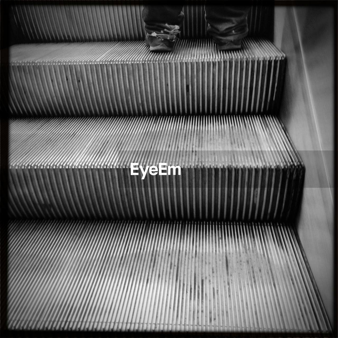 Legs Of Person On Escalator