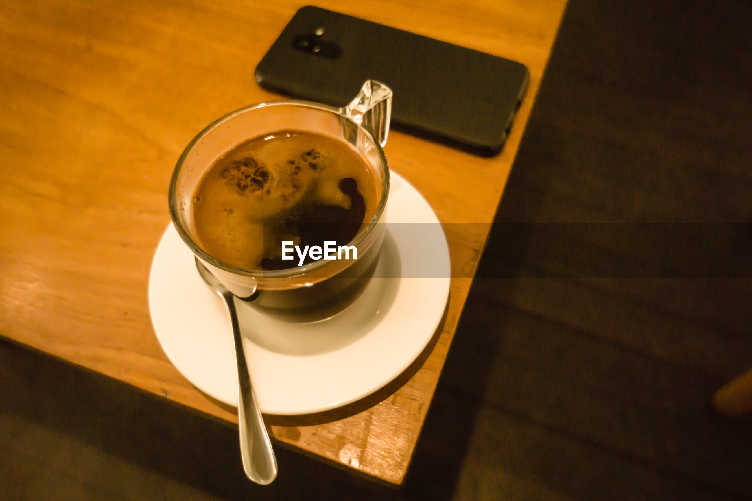 HIGH ANGLE VIEW OF COFFEE AND CUP ON WOODEN TABLE